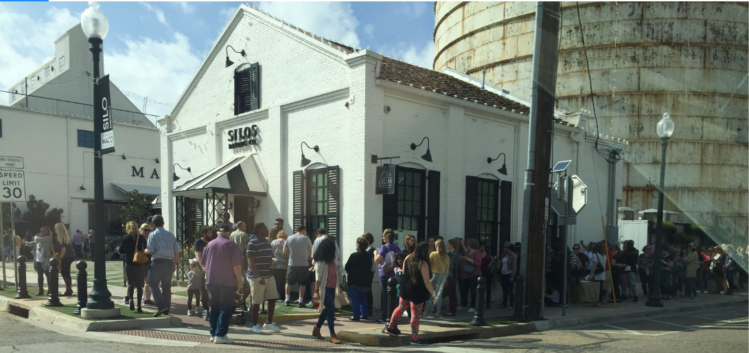 "An exterior view of a building labeled ""The Silos"" in front of a grain silo, with a crowd of people lined up outside."