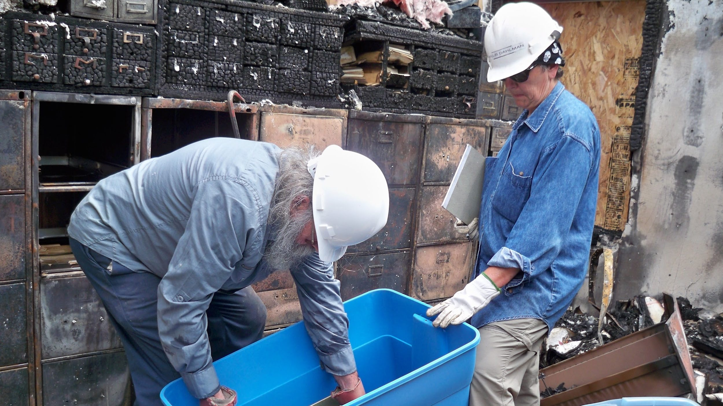 Two people stand in the midst of a destroyed collections facility, wearing hard hats and carrying a plastic bin for retrieving salvageable items.
