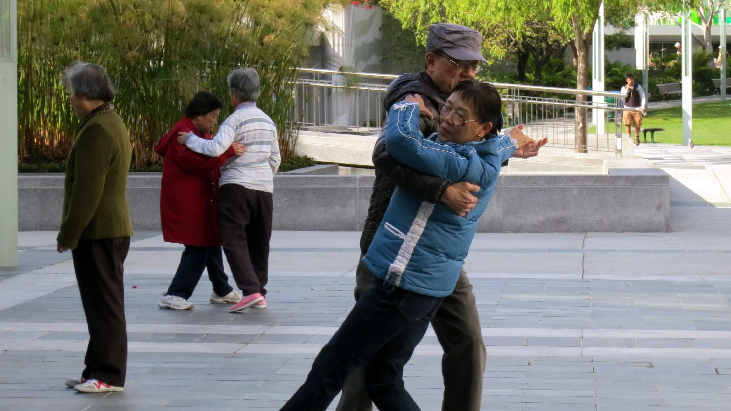 Pairs of older adults dance in an outdoor park.