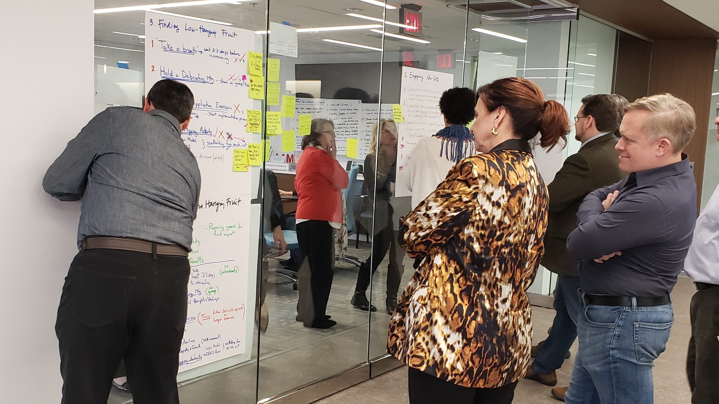 Participants in the convening stand around sheets of paper displayed on glass walls, writing and reading ideas and insights.