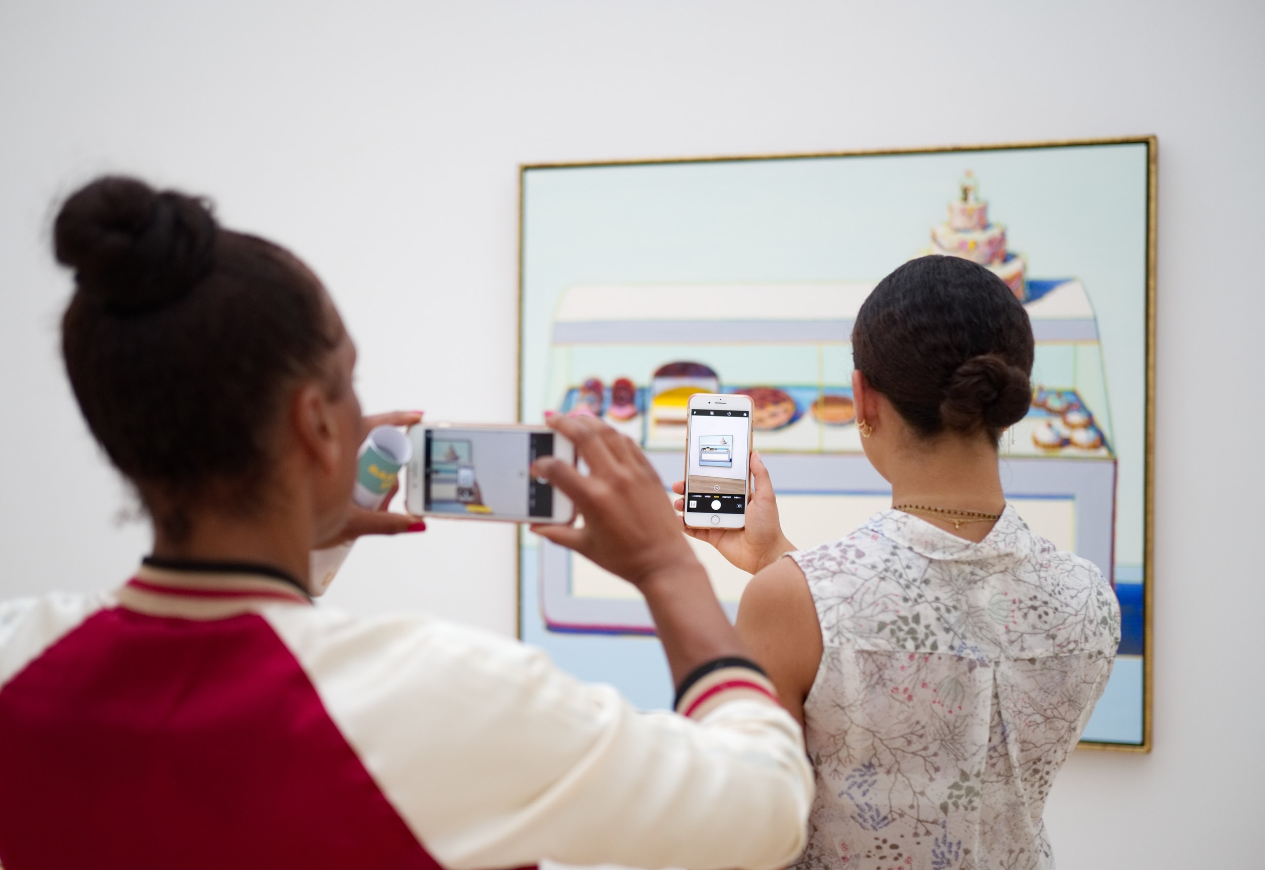 Two museum visitors hold take pictures of a Wayne Thiebaud painting on their smartphones.