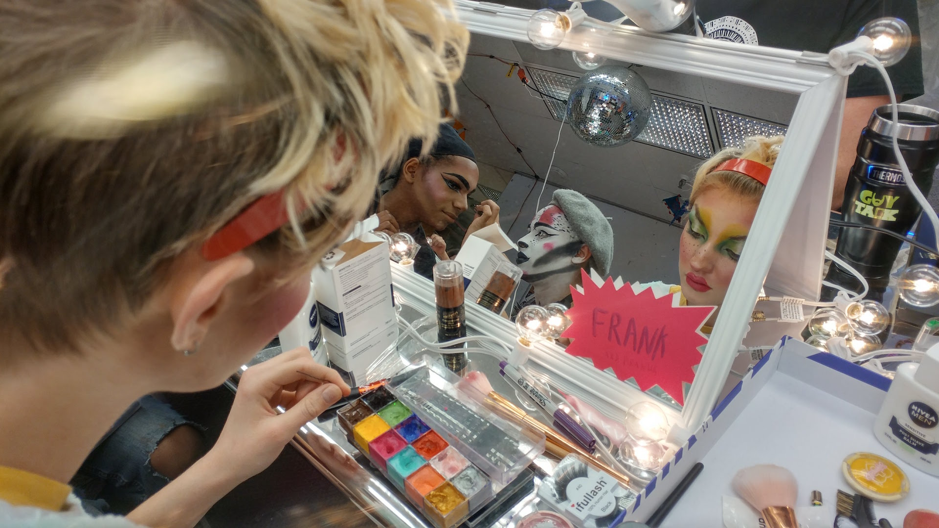 The performers are seen in a vanity mirror applying colorful and extravagant makeup looks.