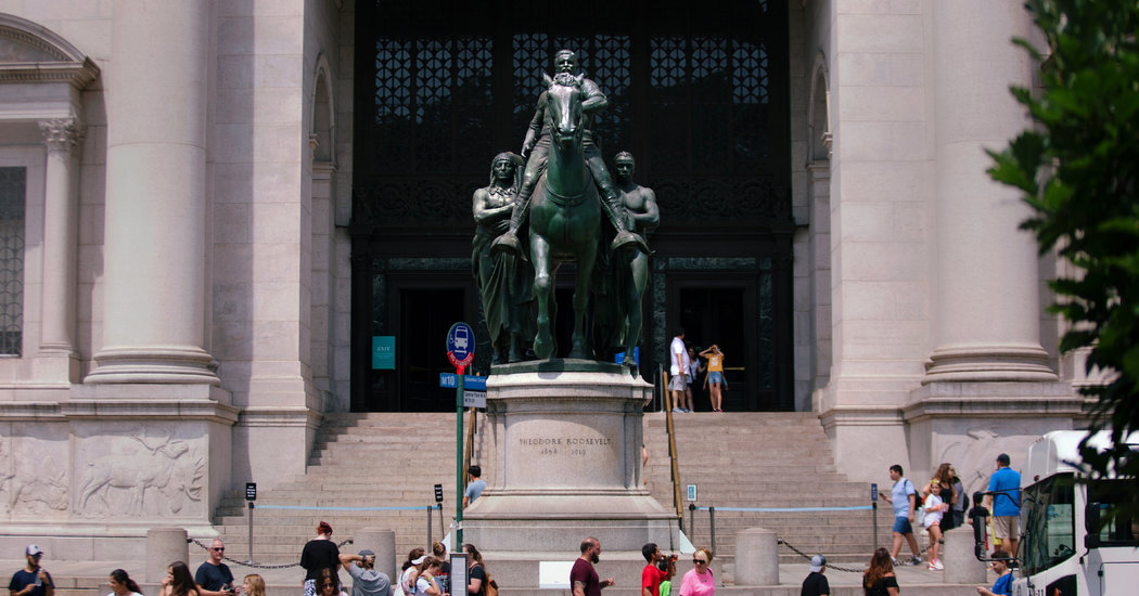 People stand outside the museum's entrance, dwarfed by the massive bronze statue of teddy Roosevelt on horseback, with a male Native American figure standing on one side and a male African American figure standing on the other.