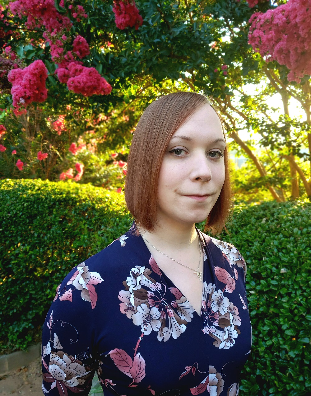 Headshot of Anna Woten standing outside in front of a flowering tree.