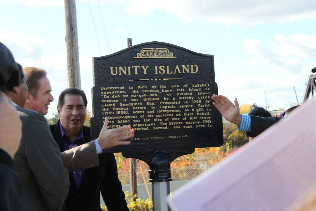"A group of people gather around a historical marker with the name ""Unity Island"" engraved on it."