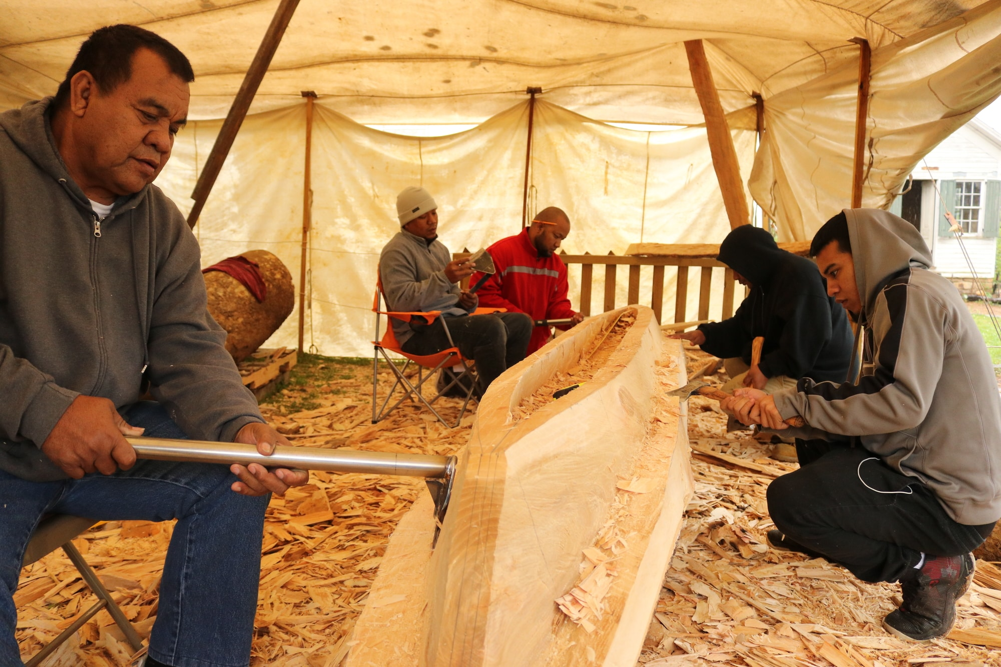 Liton and a group of four other people are seen under a tent carving the canoe, surrounded by a pile of wood shavings.
