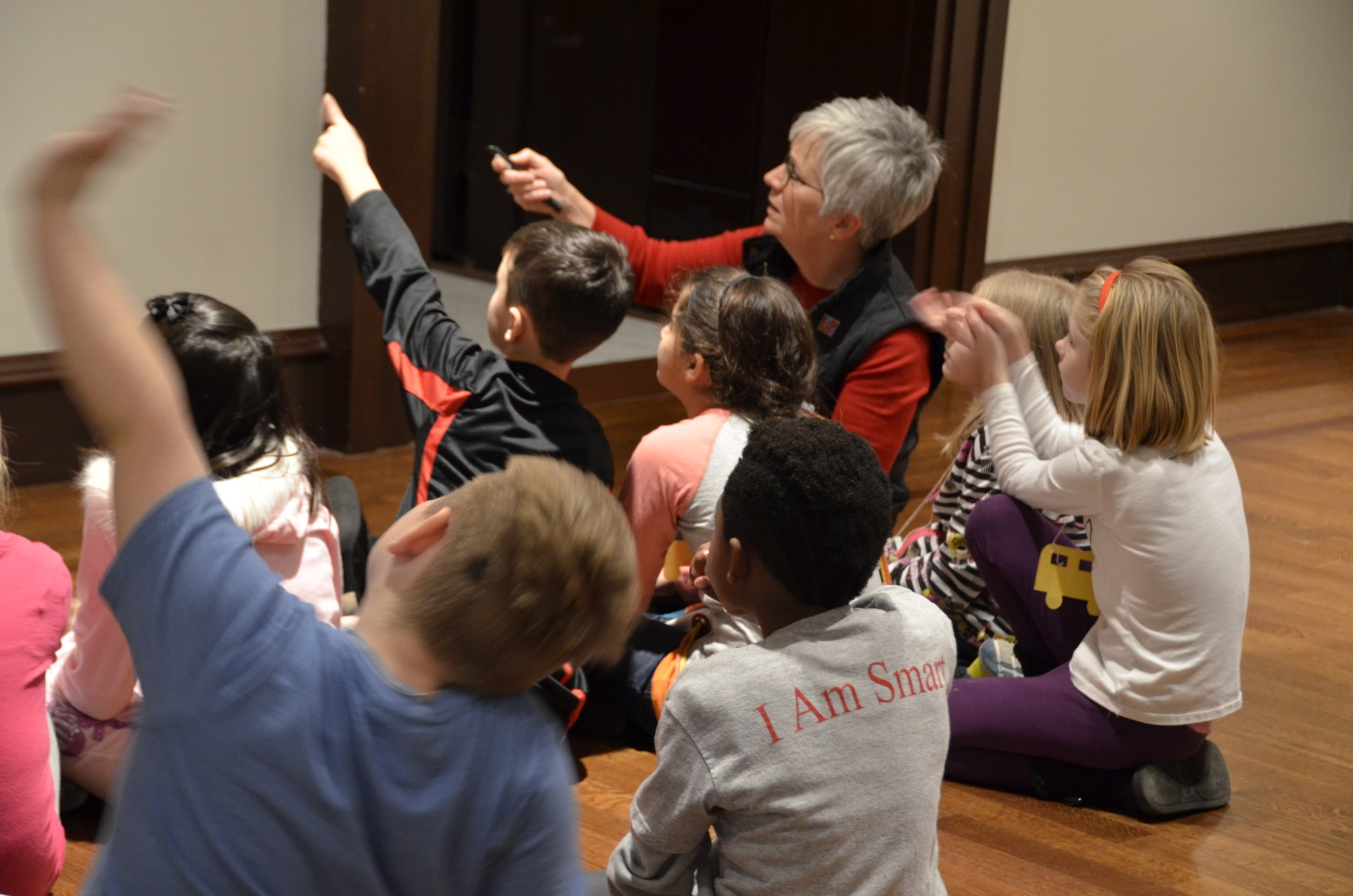 A docent is seen with a group of children seated on the floor, some of whom point in front of them to an artwork.