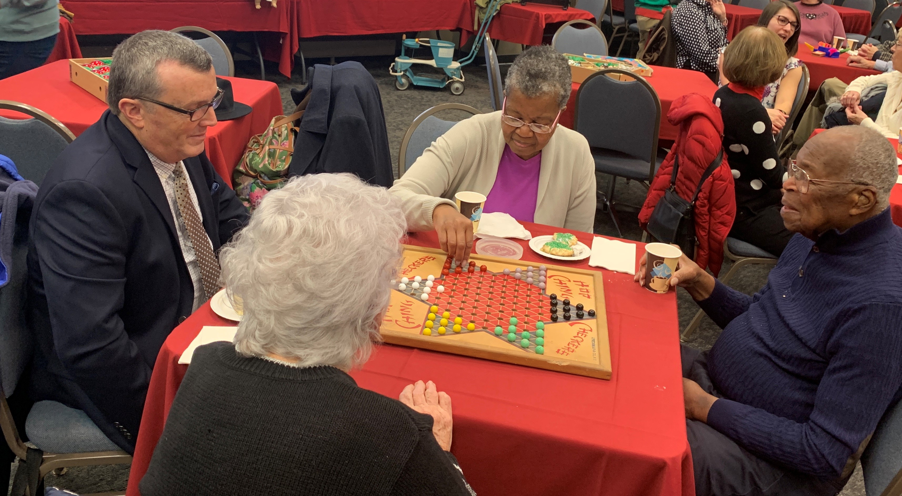 "Four people sit around a table playing ""Chinese checkers."" Other tables of people are seen in the background."