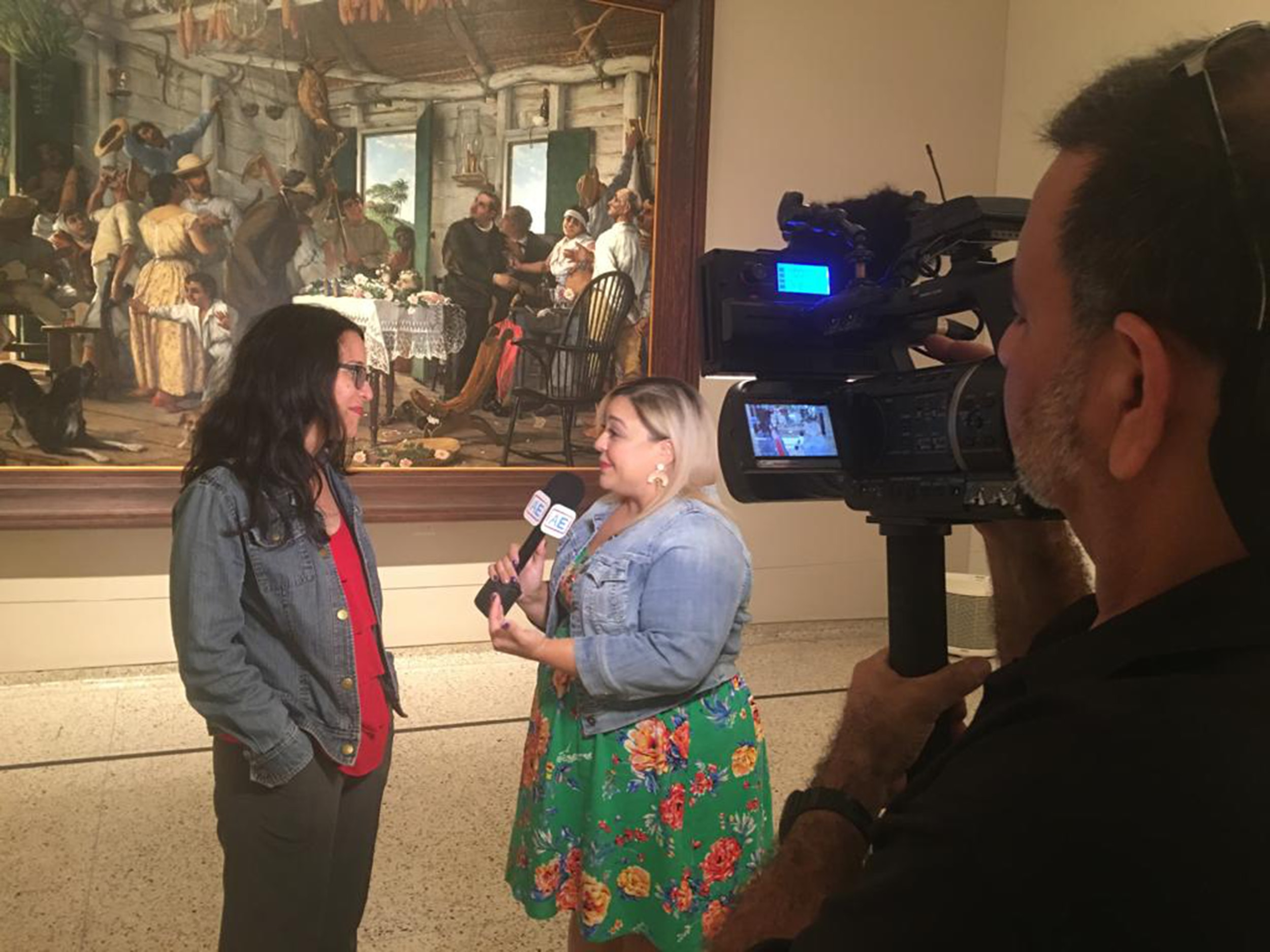 The author is seen standing in the museum talking to a reporter behind a camera.