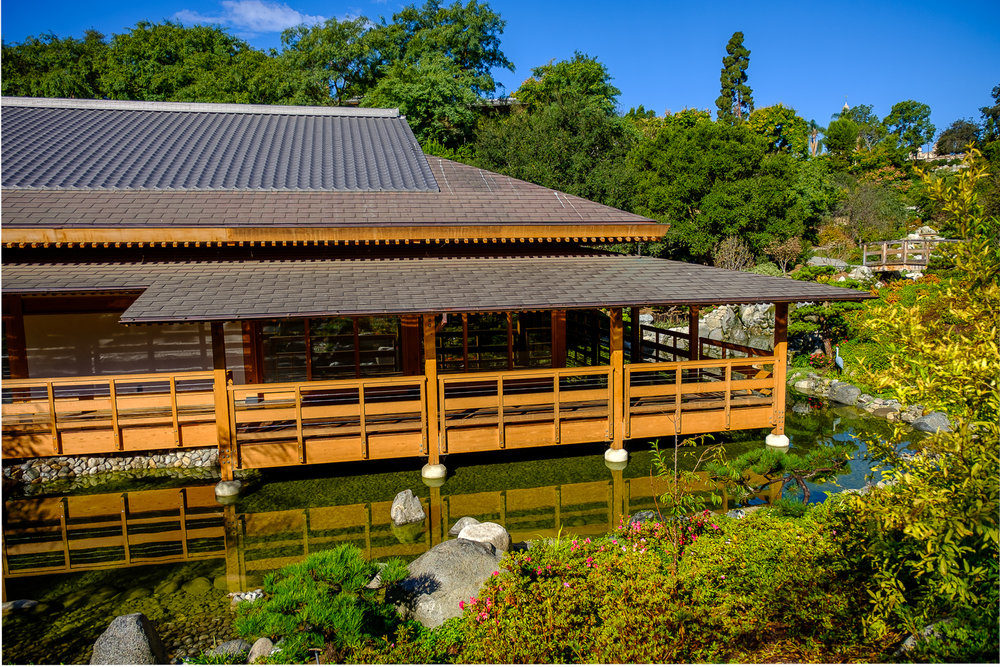 Exterior shot of a Japanese-style building surrounded by trees and gardens.