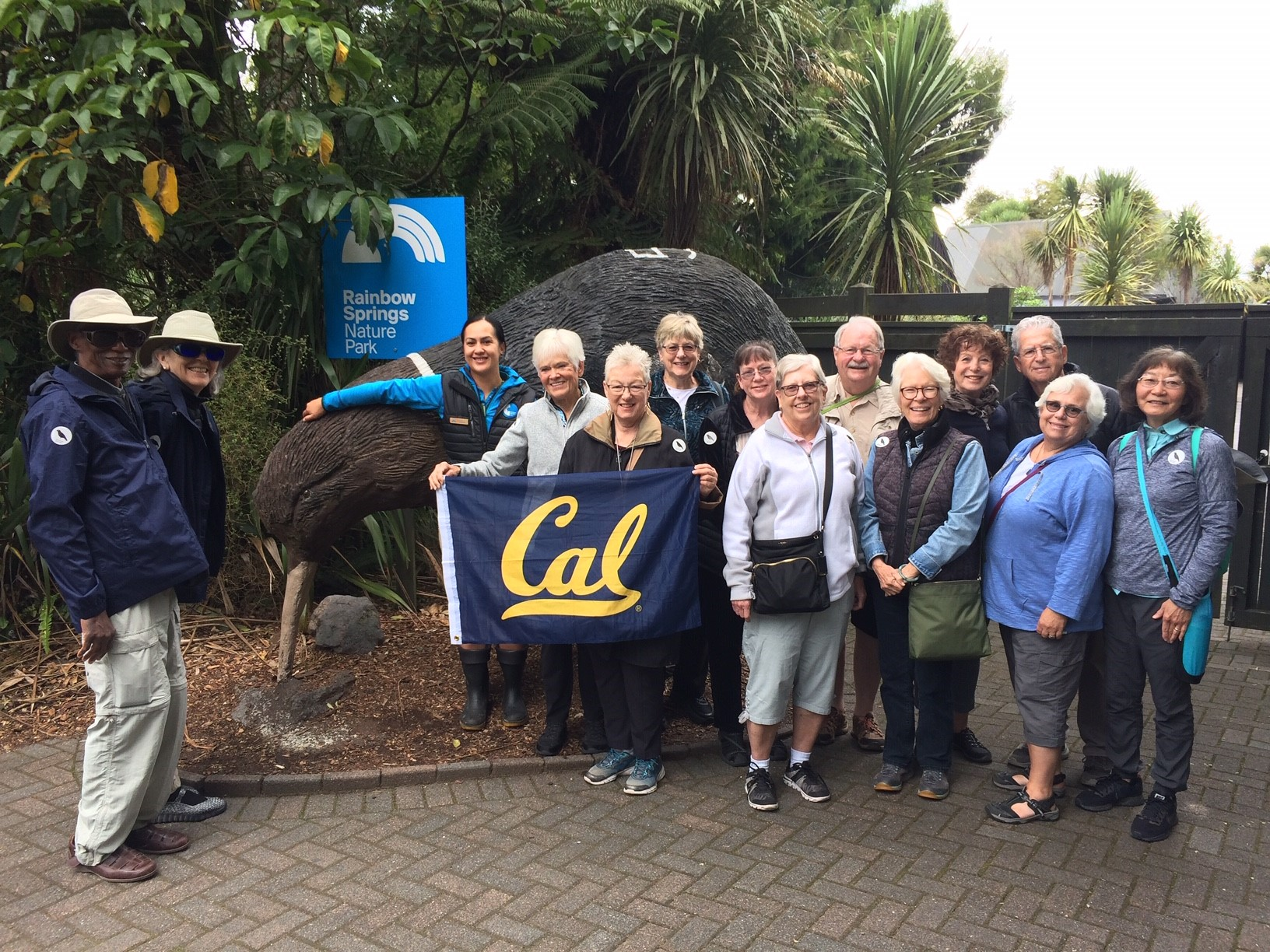 "A group of older adults poses in front of a sign that reads ""Rainbow Springs Nature Park"""