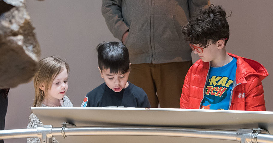 Three children gather around a display table inside a museum, while an adult stands behind them.