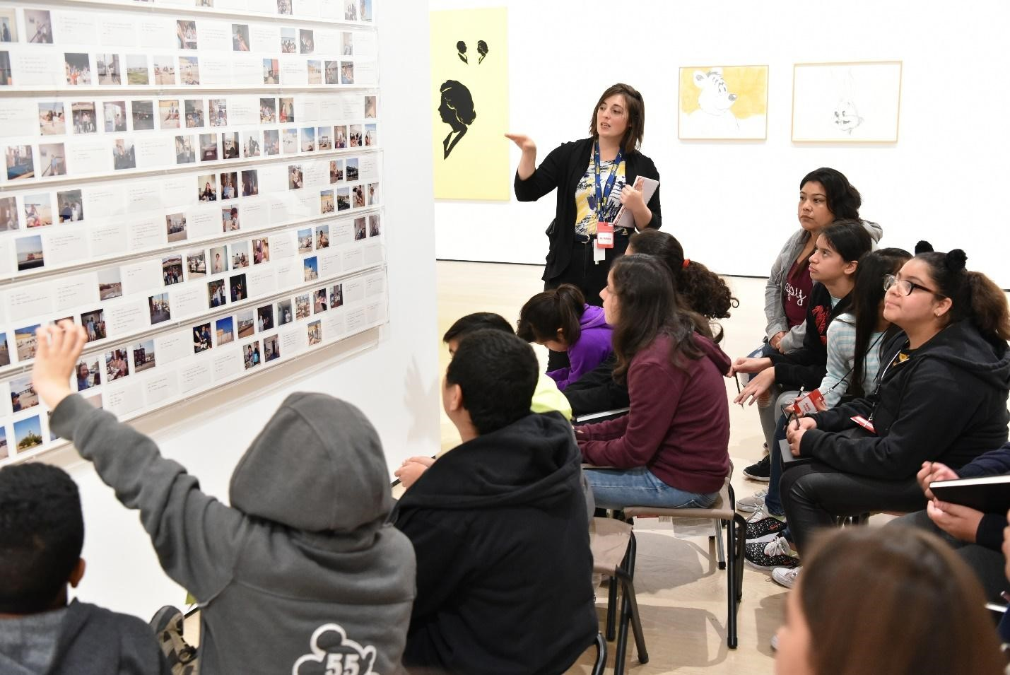 An instructor leads a group of children in a discussion of a work of art on display.