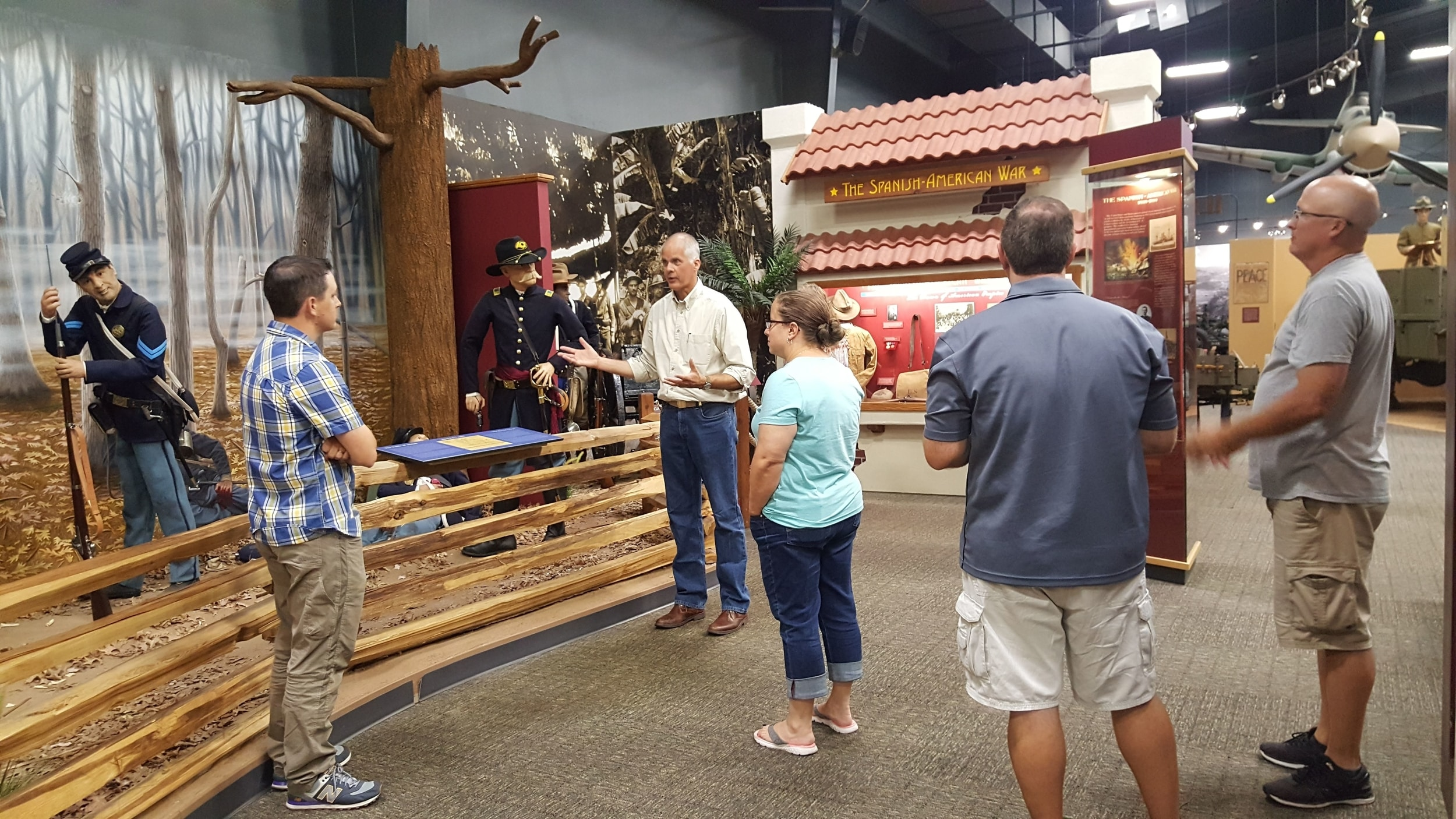 A group of participants stands around a display on the Spanish-American War