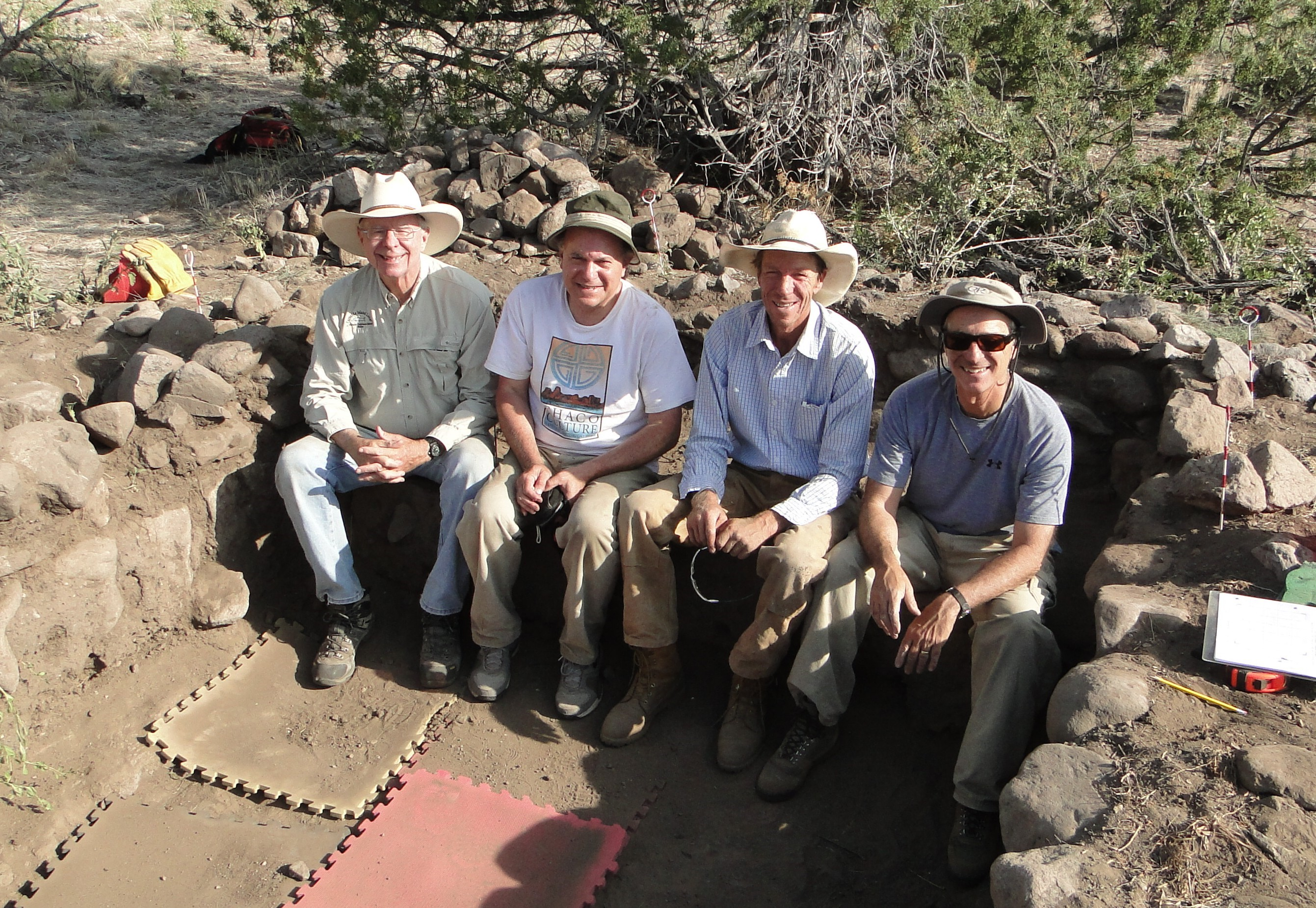 Four team members pose sitting in a recess in the earth surrounded by stone foundation.