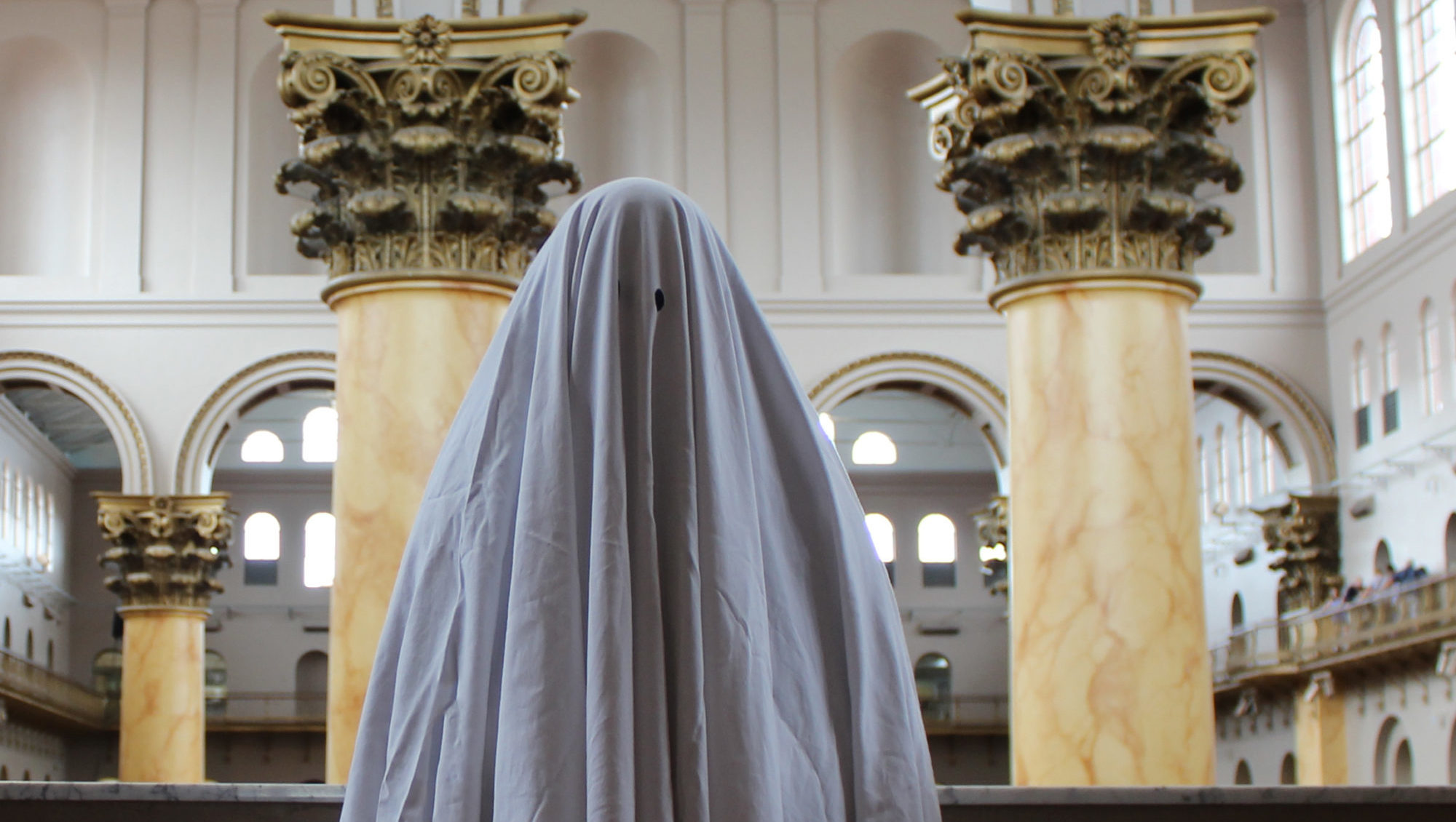 A sheet-with-eye-holes ghost stands in the middle of a historic museum building.