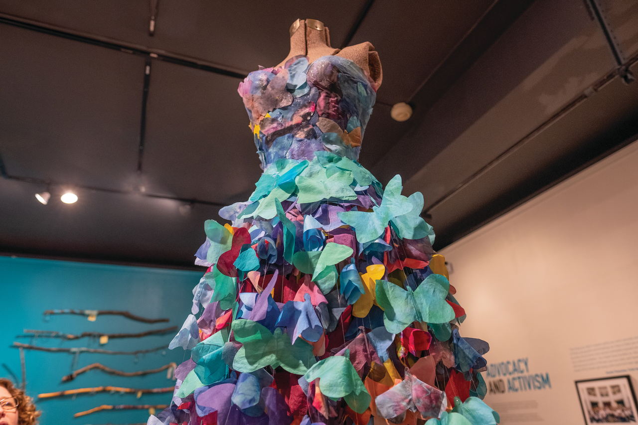 A mannequin figure in a dress made from many different colored paper butterflies.