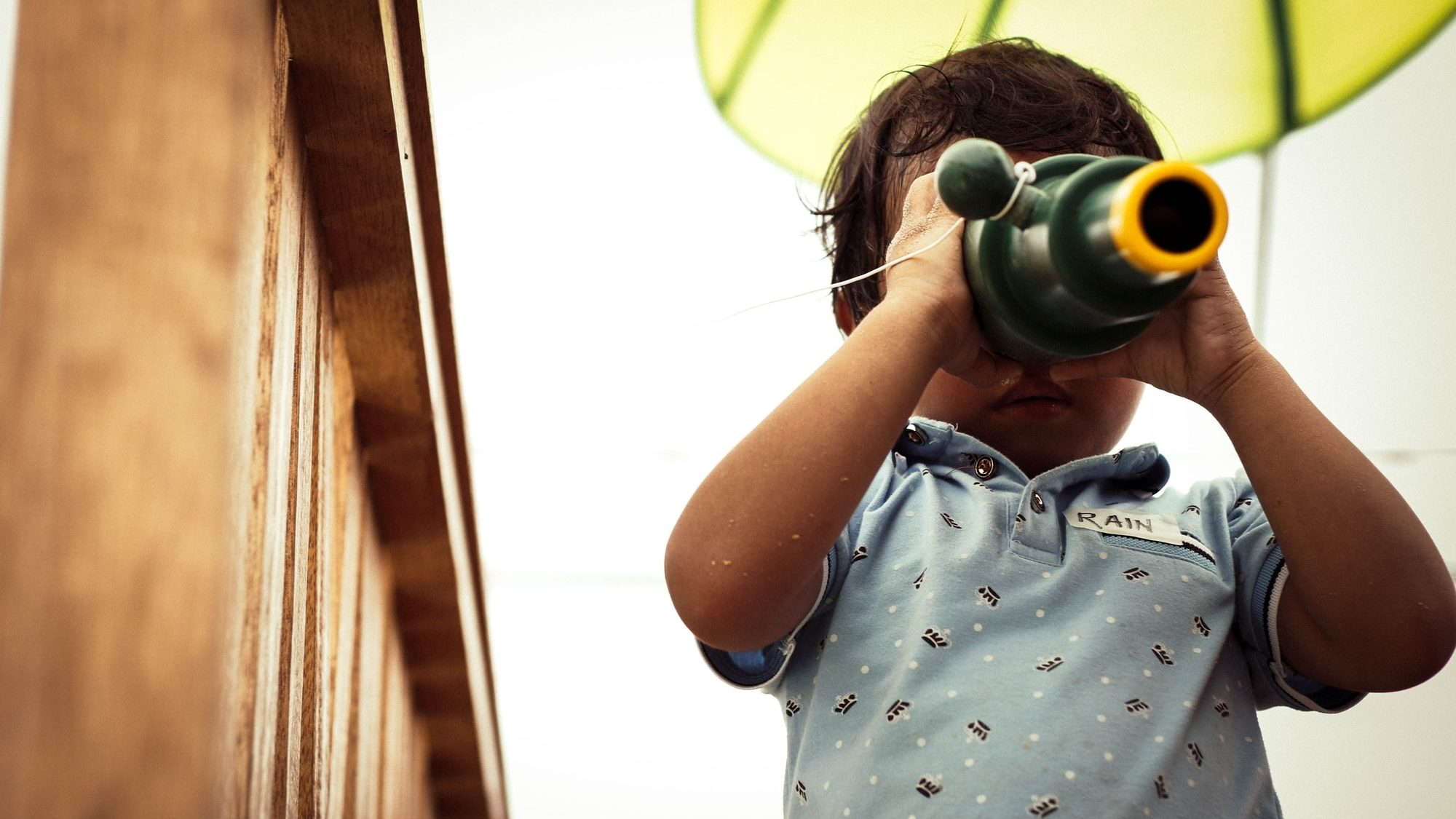 A young child looks through binoculars.