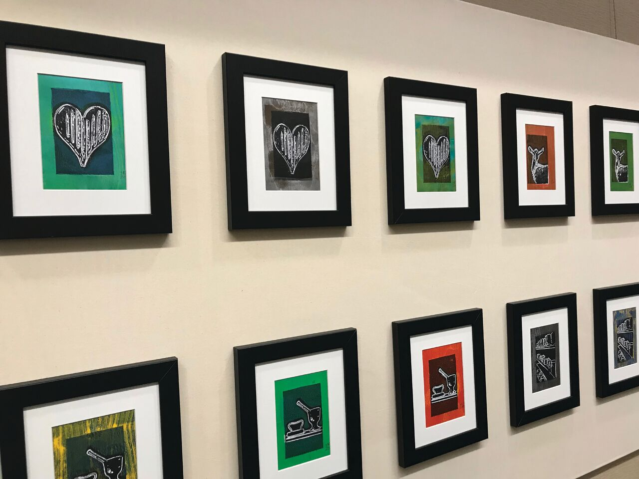 A row of framed artwork hung parallel on a wall.