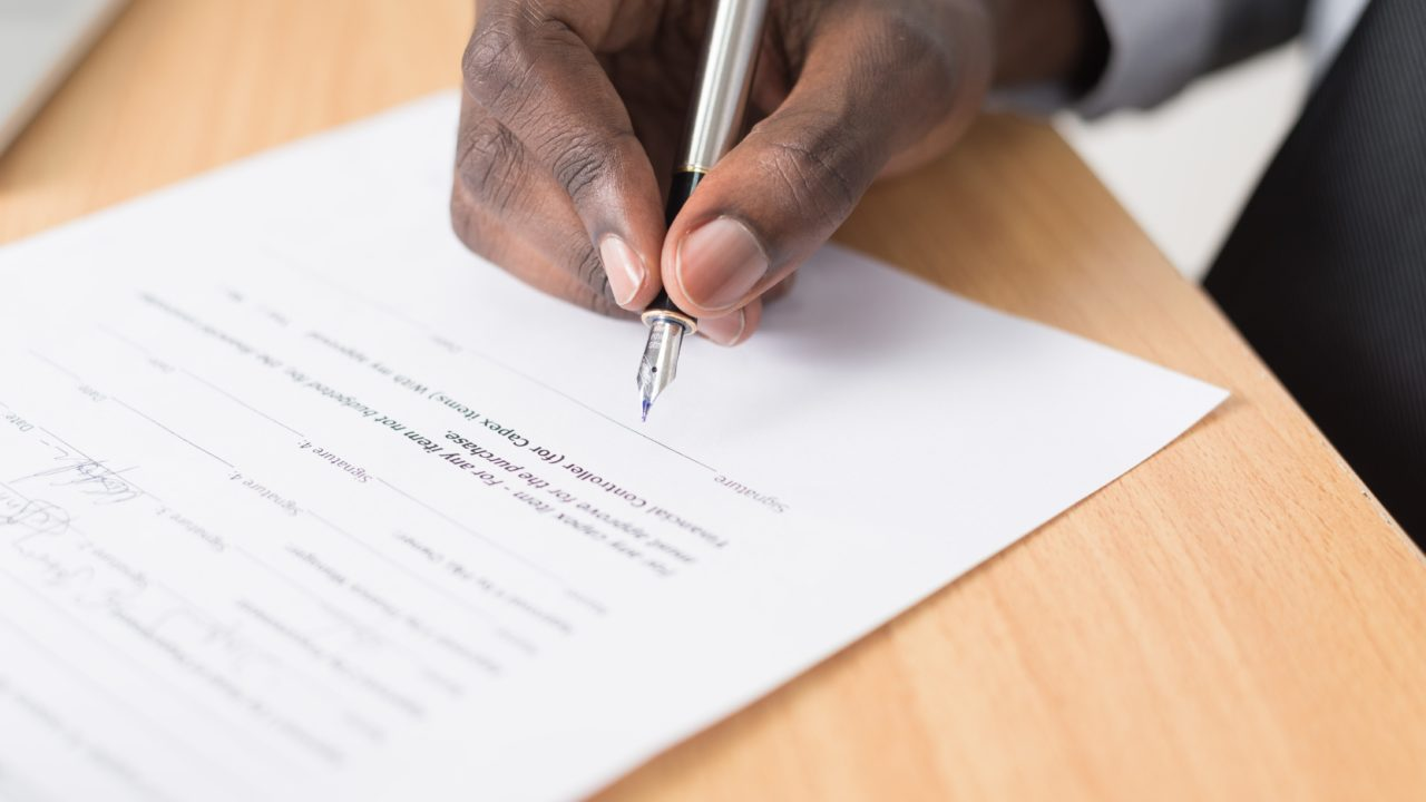 A person holding a pen to sign a contract.