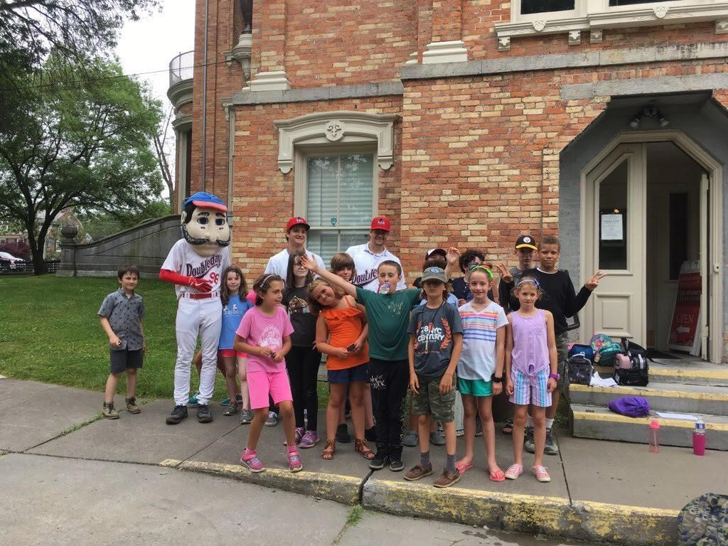 Campers pose for a group portrait in front of a museum with someone in an Abner Doubleday costume.