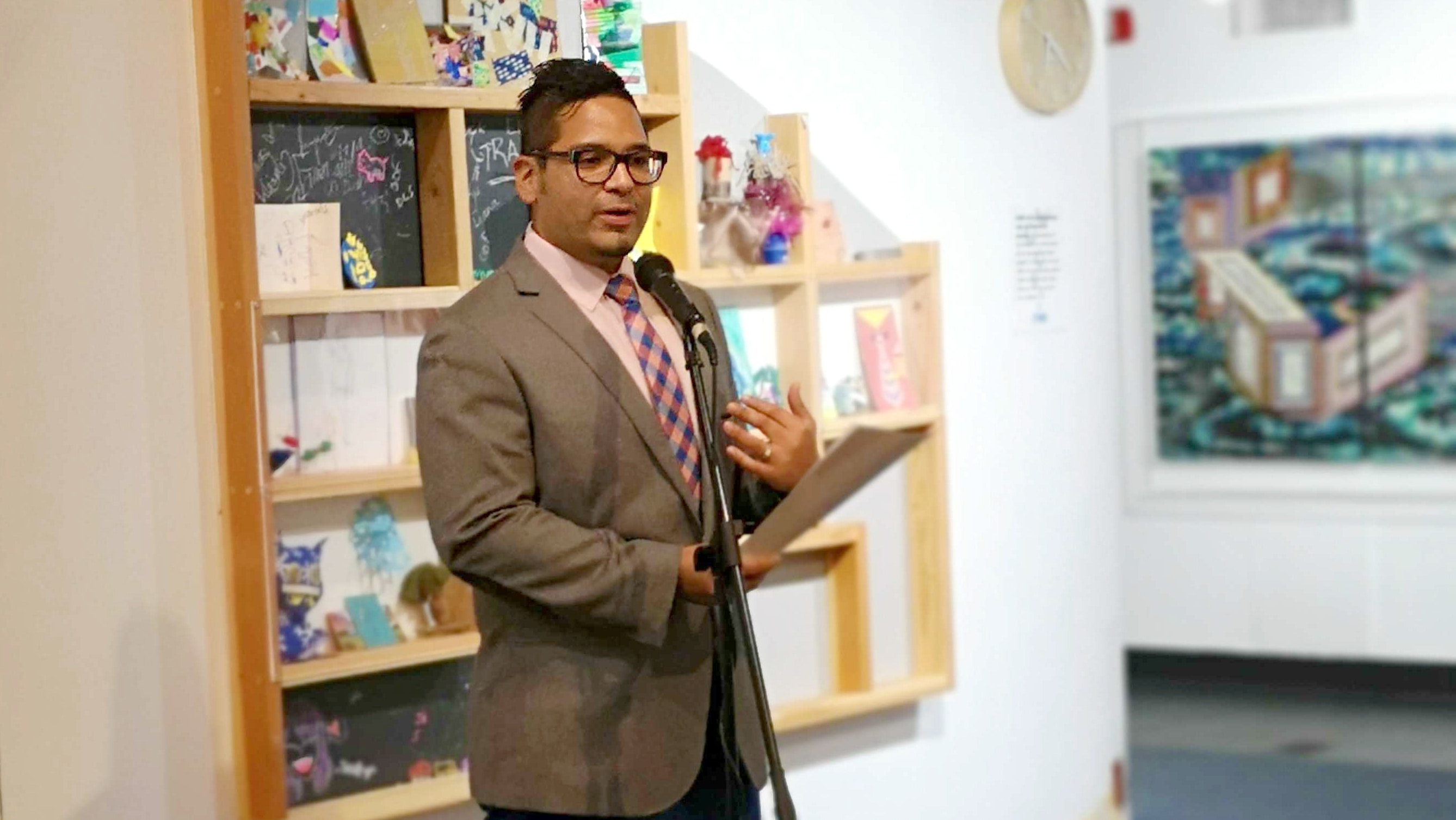 David Rios speaking at a microphone inside of a children's museum space.