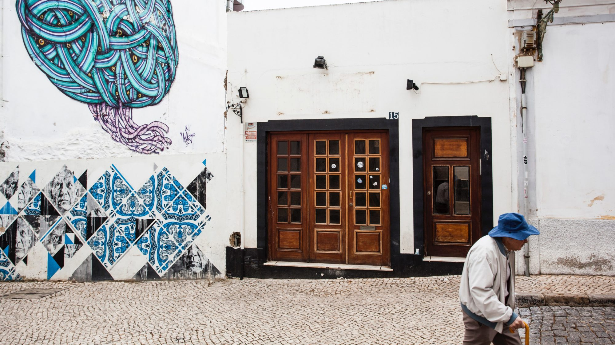 An older person walks past a building decorated with street art.