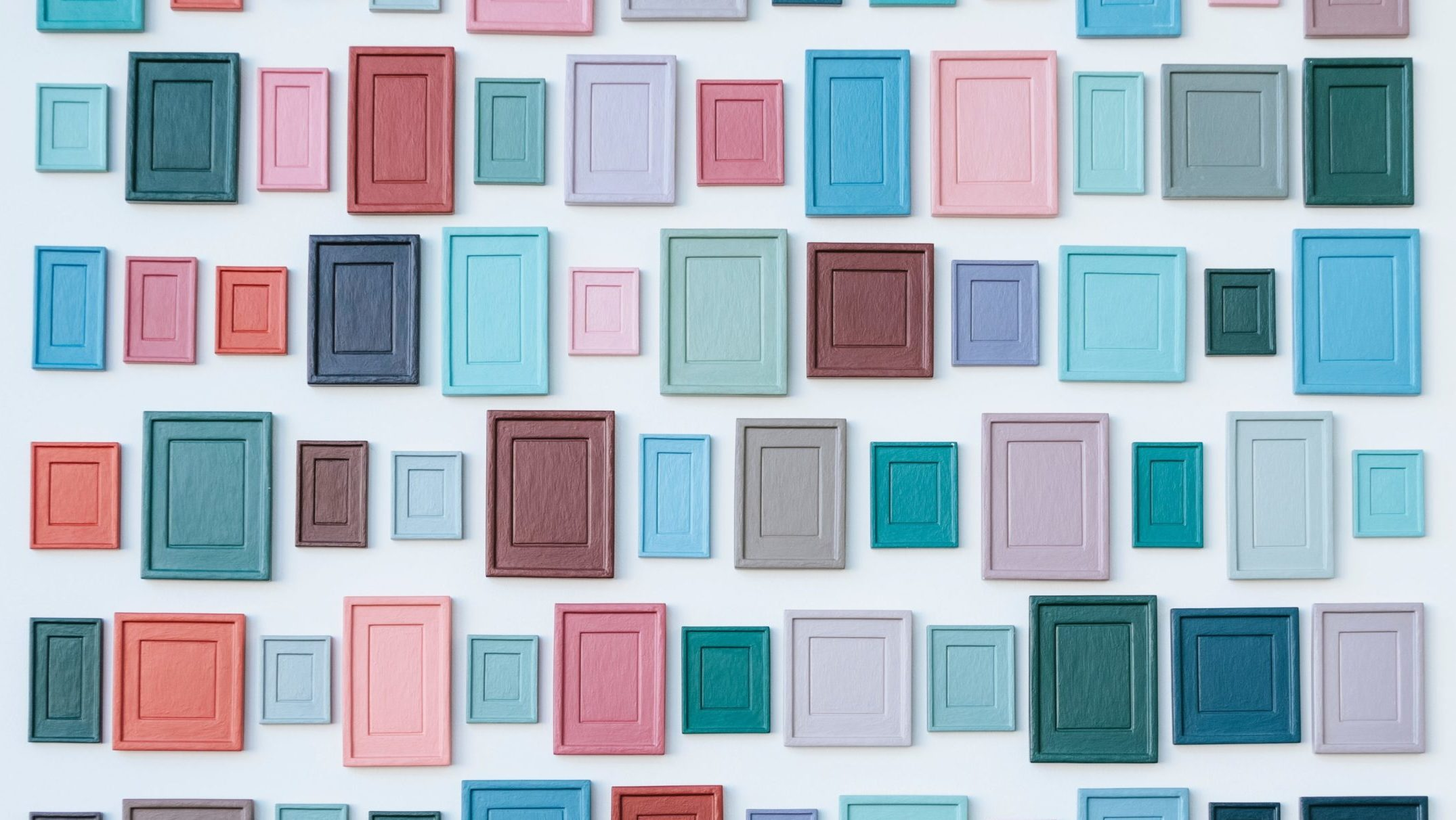 A wall of empty frames in a variety of sizes and colors.