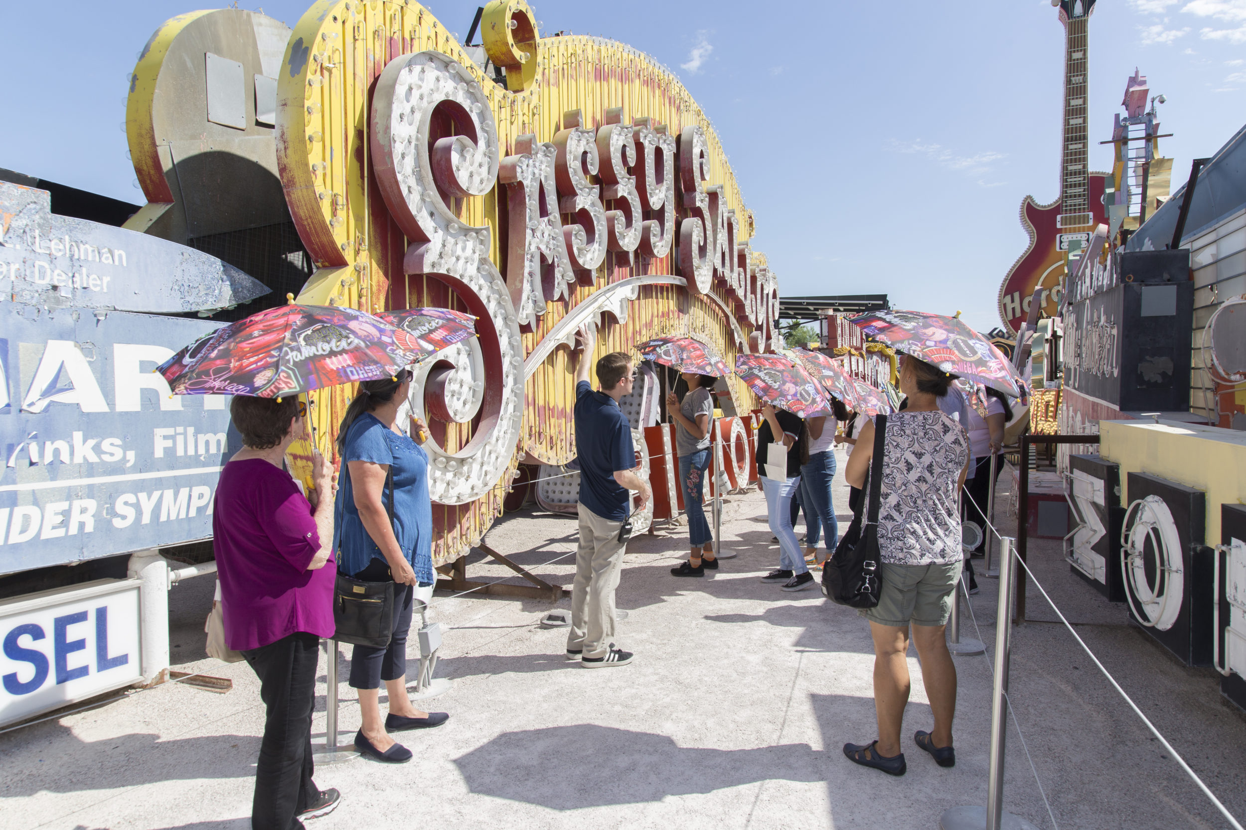 "A group of people holding parasols stands outdoors in front of a large neon sign that says ""Sassy."""