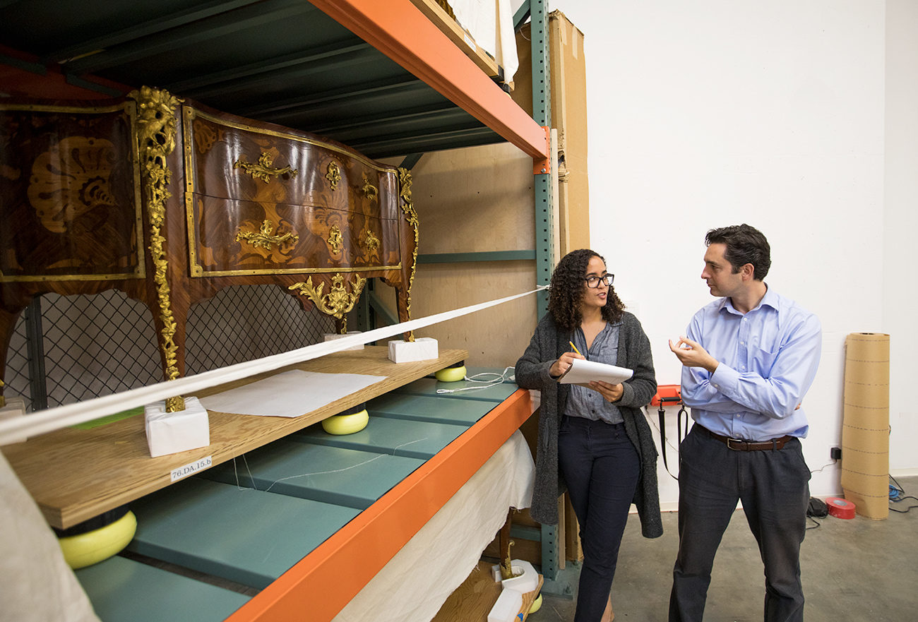 Two museum professionals stand in a collections store space.