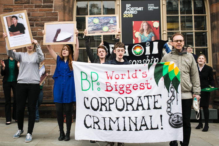 "A group of individuals stand with protest signs the largest of which says, ""BP: World's Biggest Corporate Criminal!"""