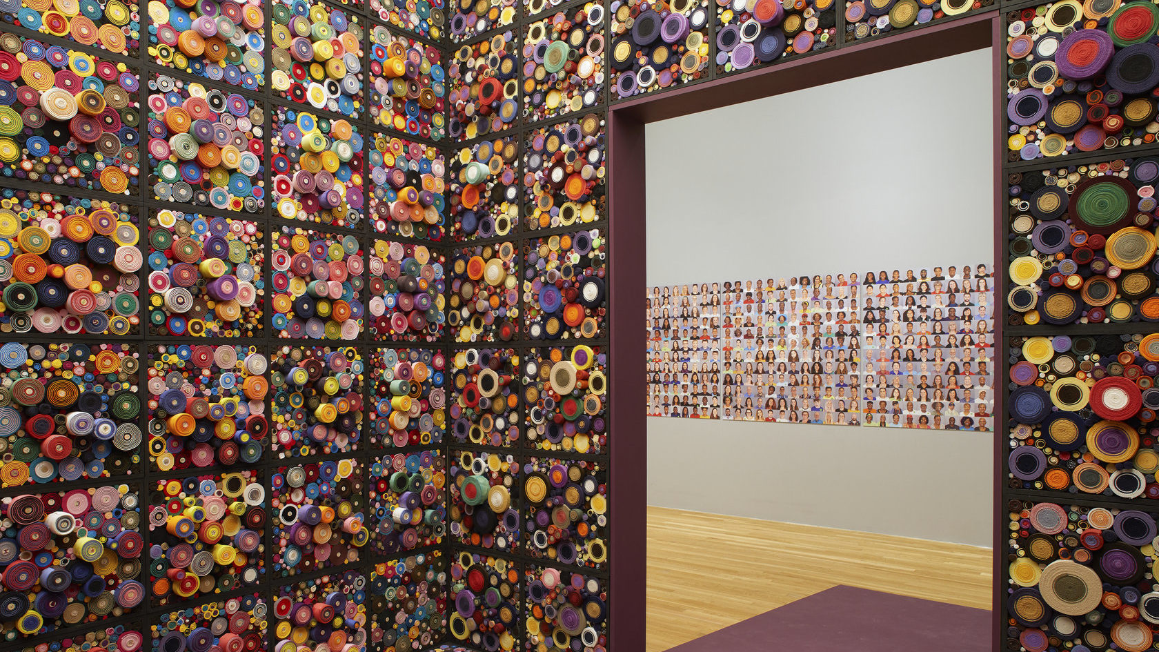 An immersion room inside of a museum gallery has cubes of textured, colorful bundles around the walls, and a grid of portraits is visible in the gallery beyond the door.