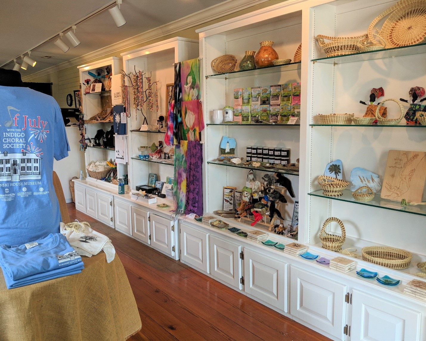 Interior of a museum store with objects like woven baskets and museum t-shirts on sale.