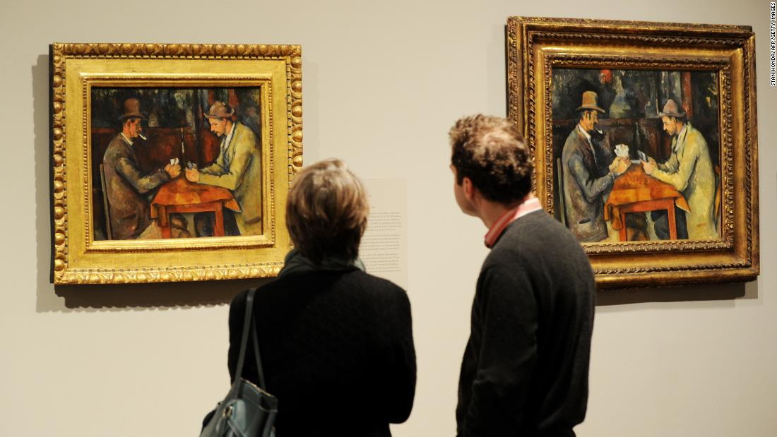 2 people looking at a painting