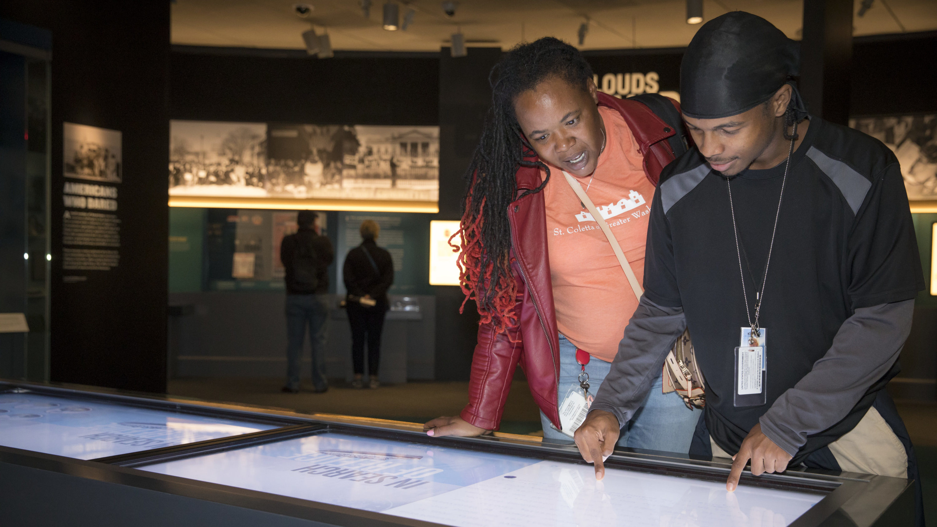 Two people bent over an interactive display table in a museum gallery.