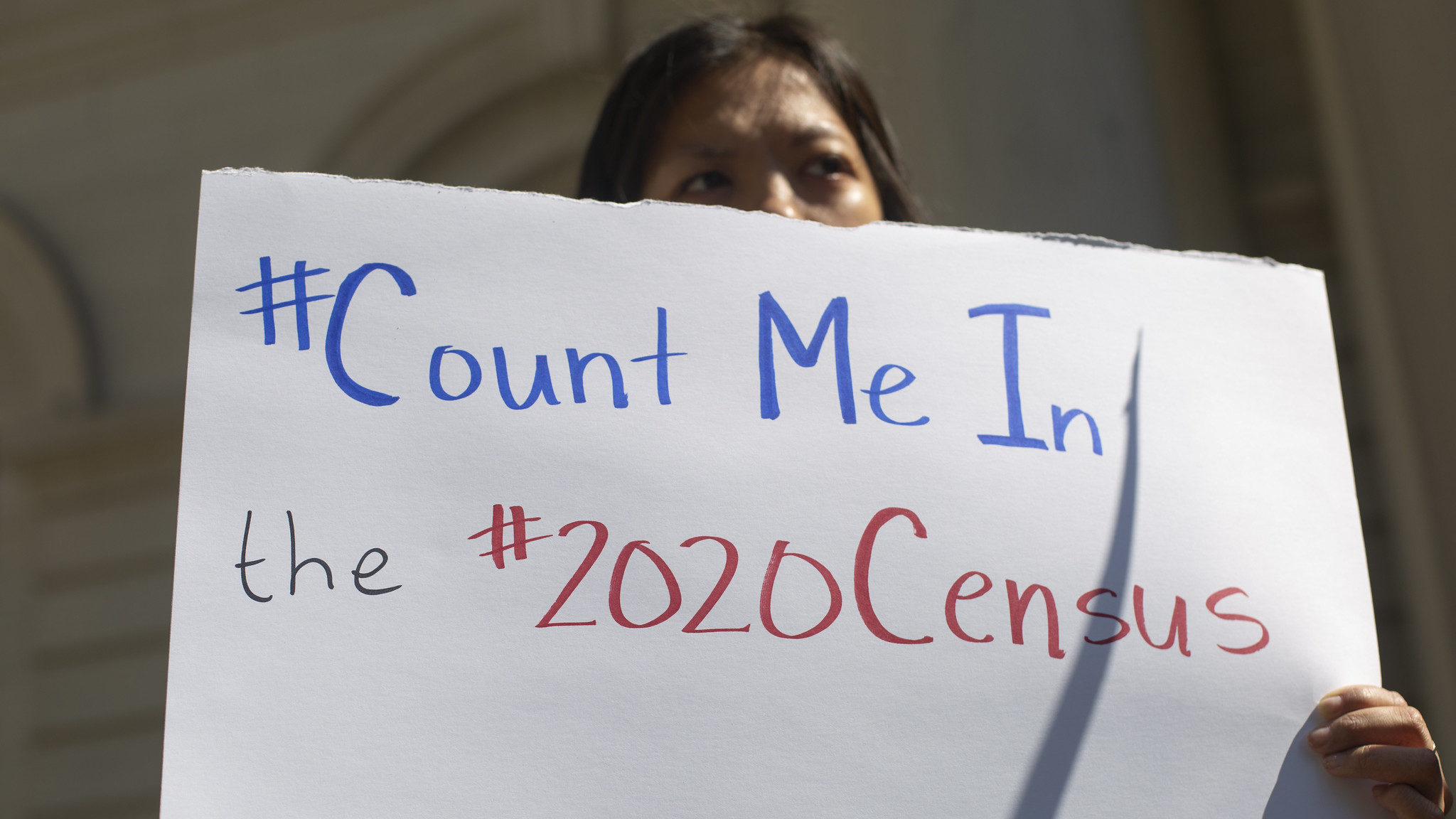 "A protester behind a sign that says ""#Count Me In the #2020Census. #lovetransforms."""