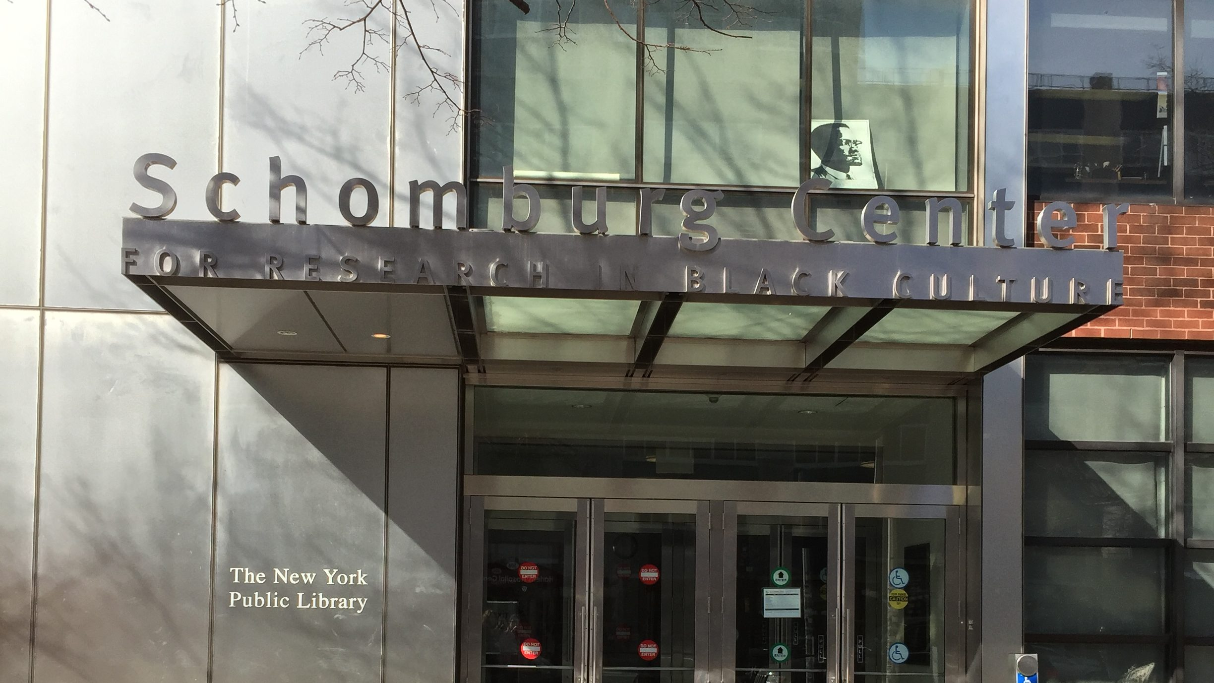 "The facade of a building with a sign that reads ""Schomburg Center for Research in Black Culture,"" with ""The New York Public Library"" underneath."