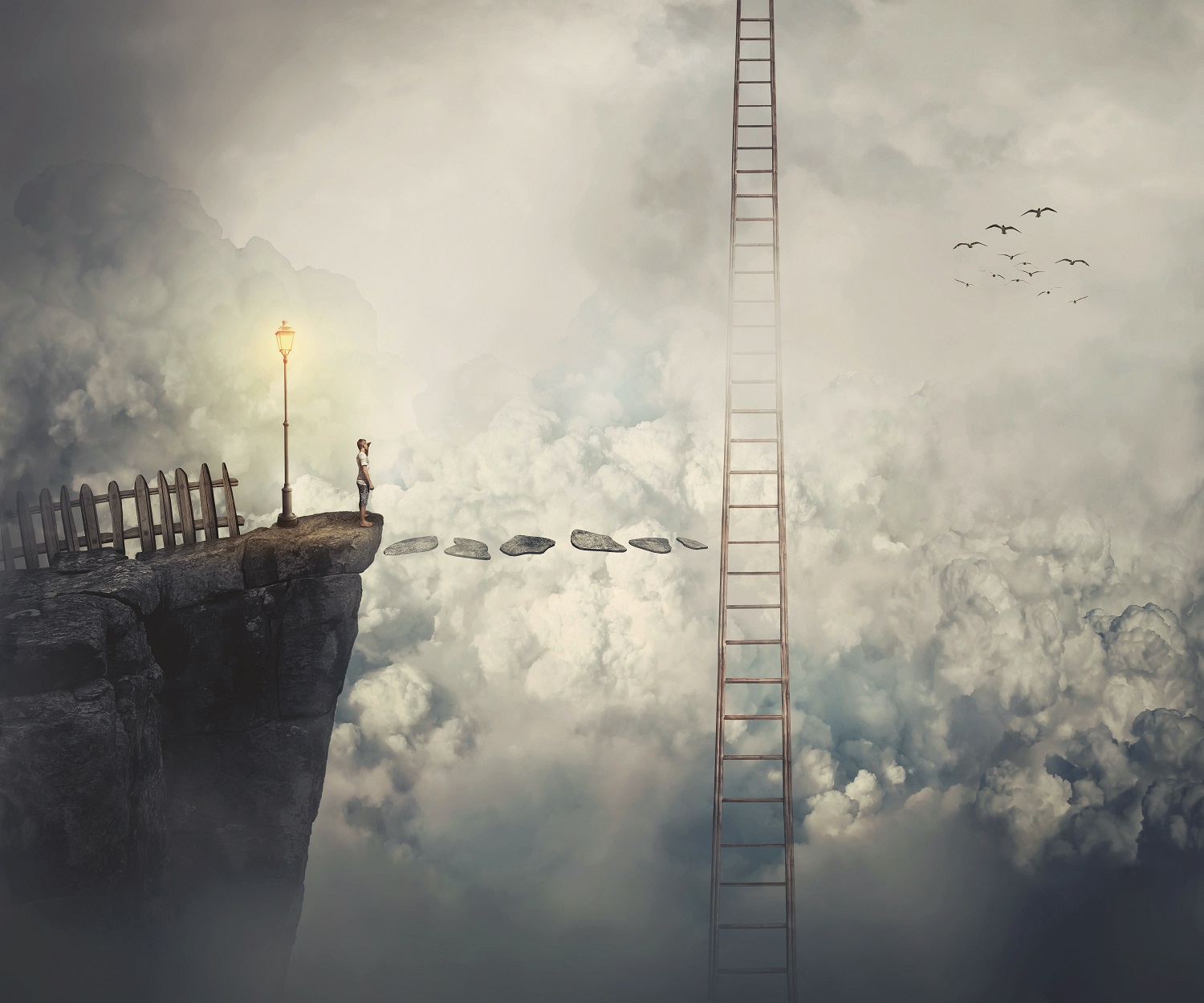 A person stands on a precipice looking out into an abyss of clouds with a single ladder leading toward the sky about halfway across the chasm.