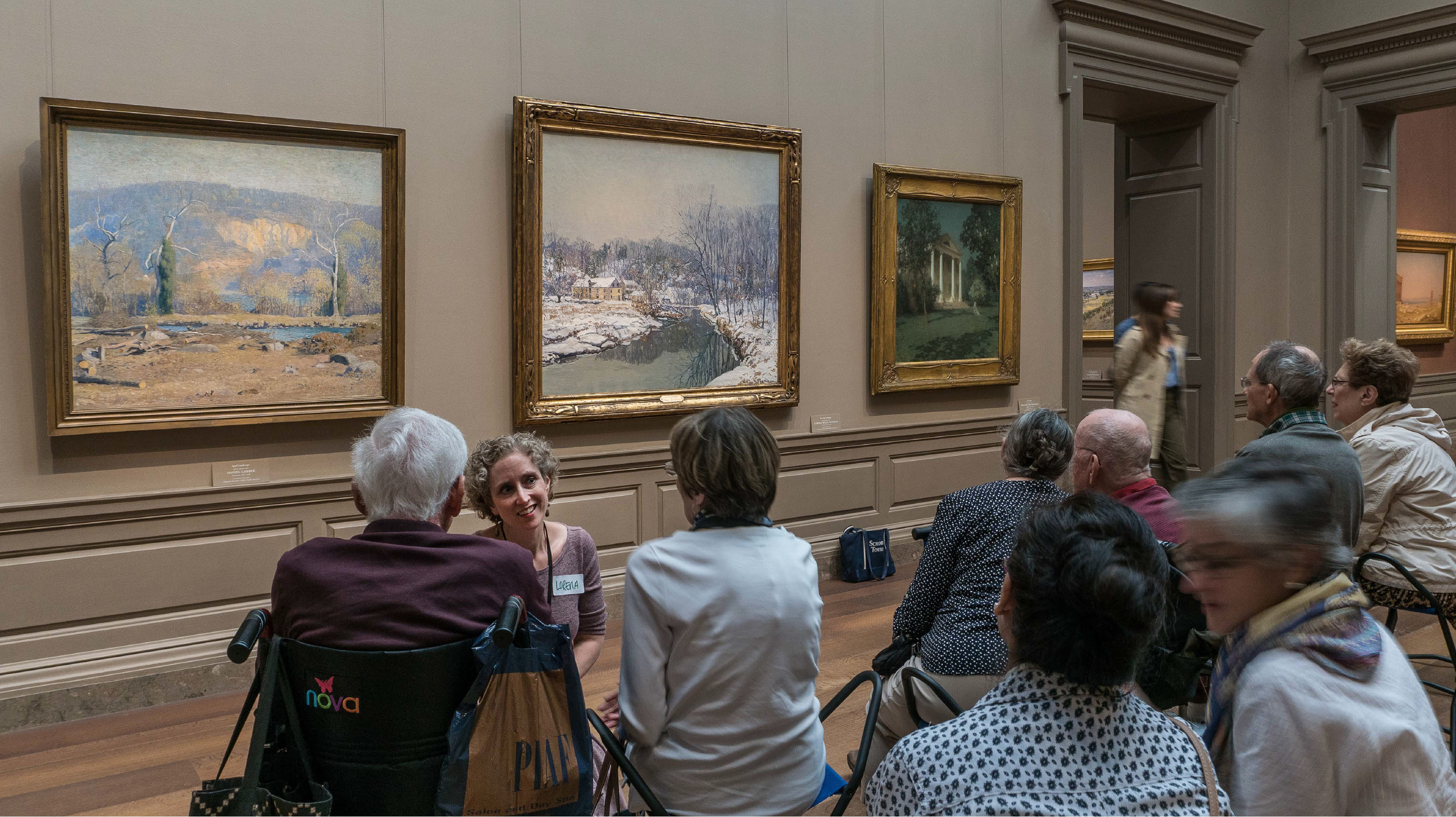In a museum gallery in front of paintings, an educator kneels down talking to a group of program participants, one of whom is seated in a wheelchair.