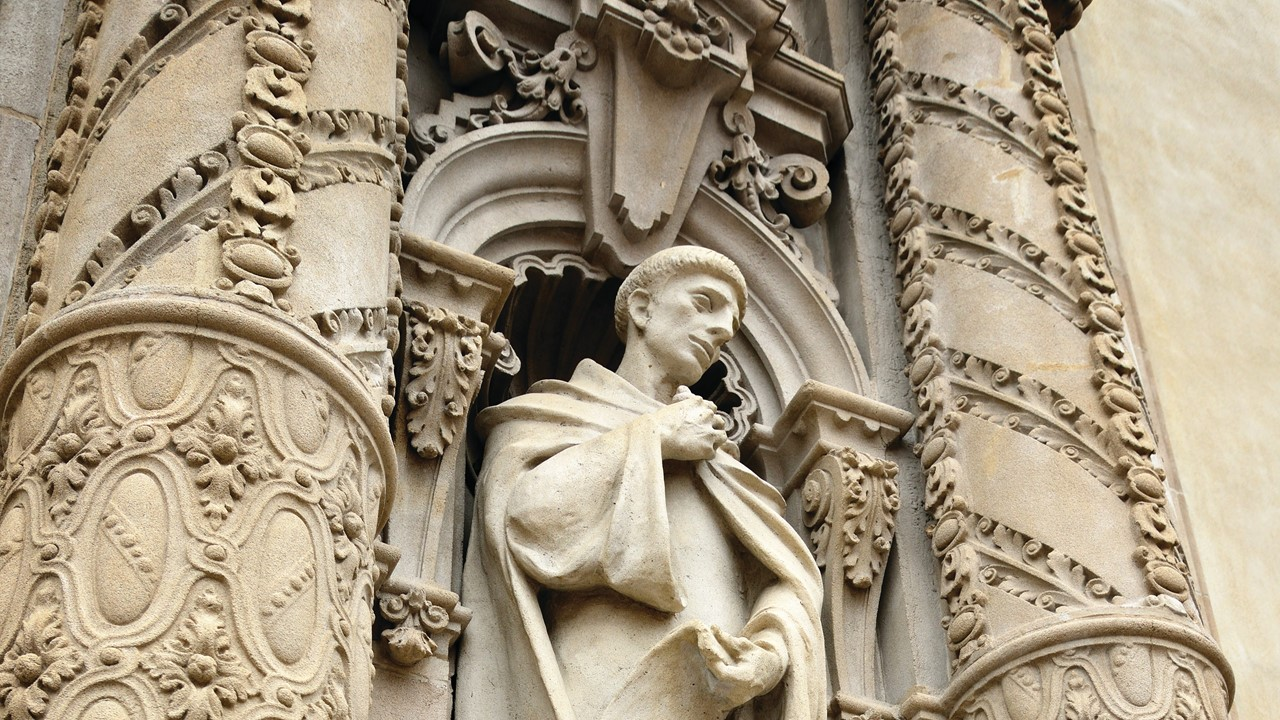 A marble sculpture of a monk on the museum's facade.