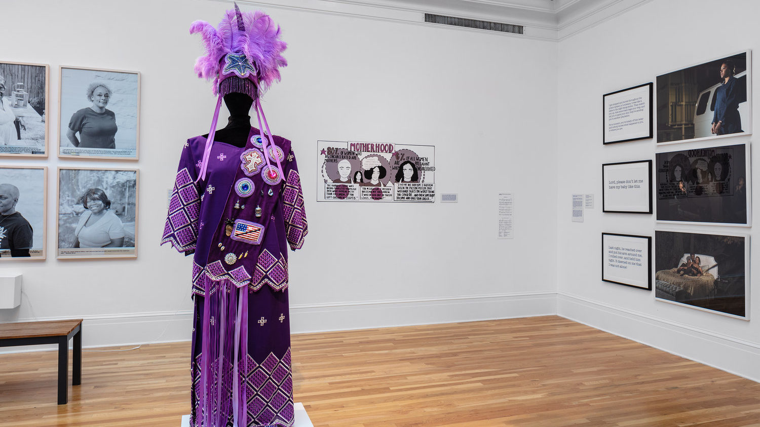 Artworks in a museum gallery, including photographed portraits and a purple dress and feathered headpiece on a mannequin