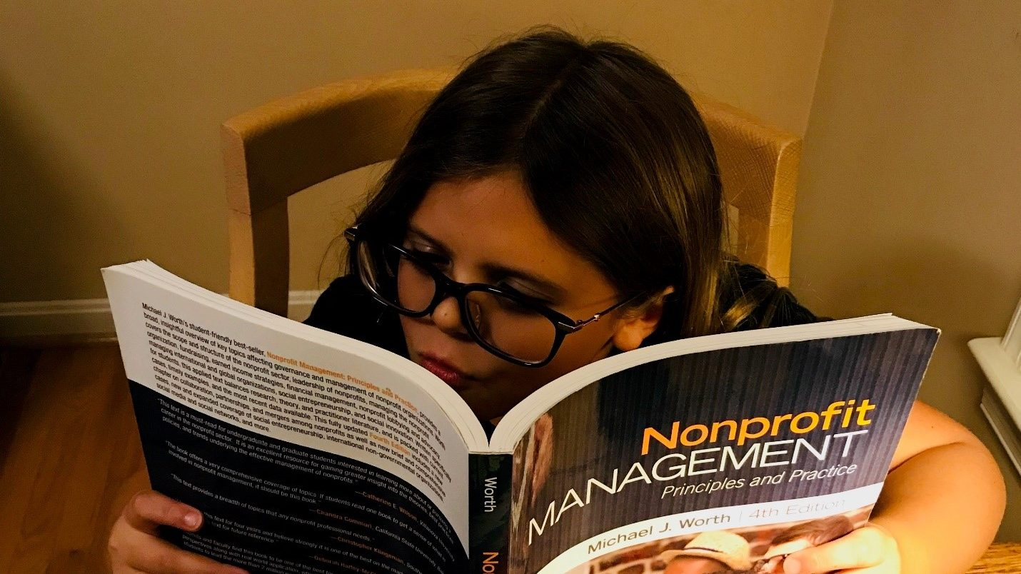"A child sits reading a book called ""Nonprofit Management."""