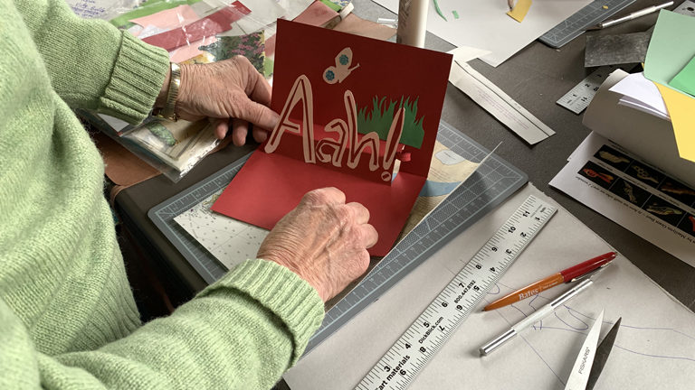 "A program participant's art project, a card that says ""Aah!"" with a picture of a butterfly and grass"