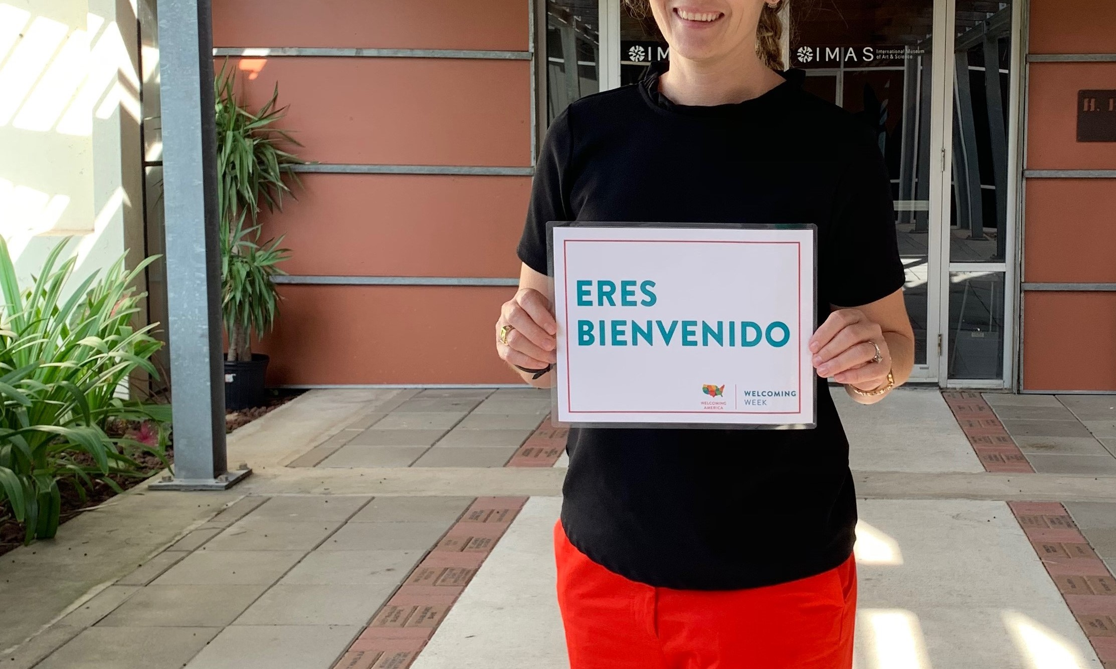 "A person stands at the front entrance of the museum holding up a sign that says ""ERES BIENVENIDO."""