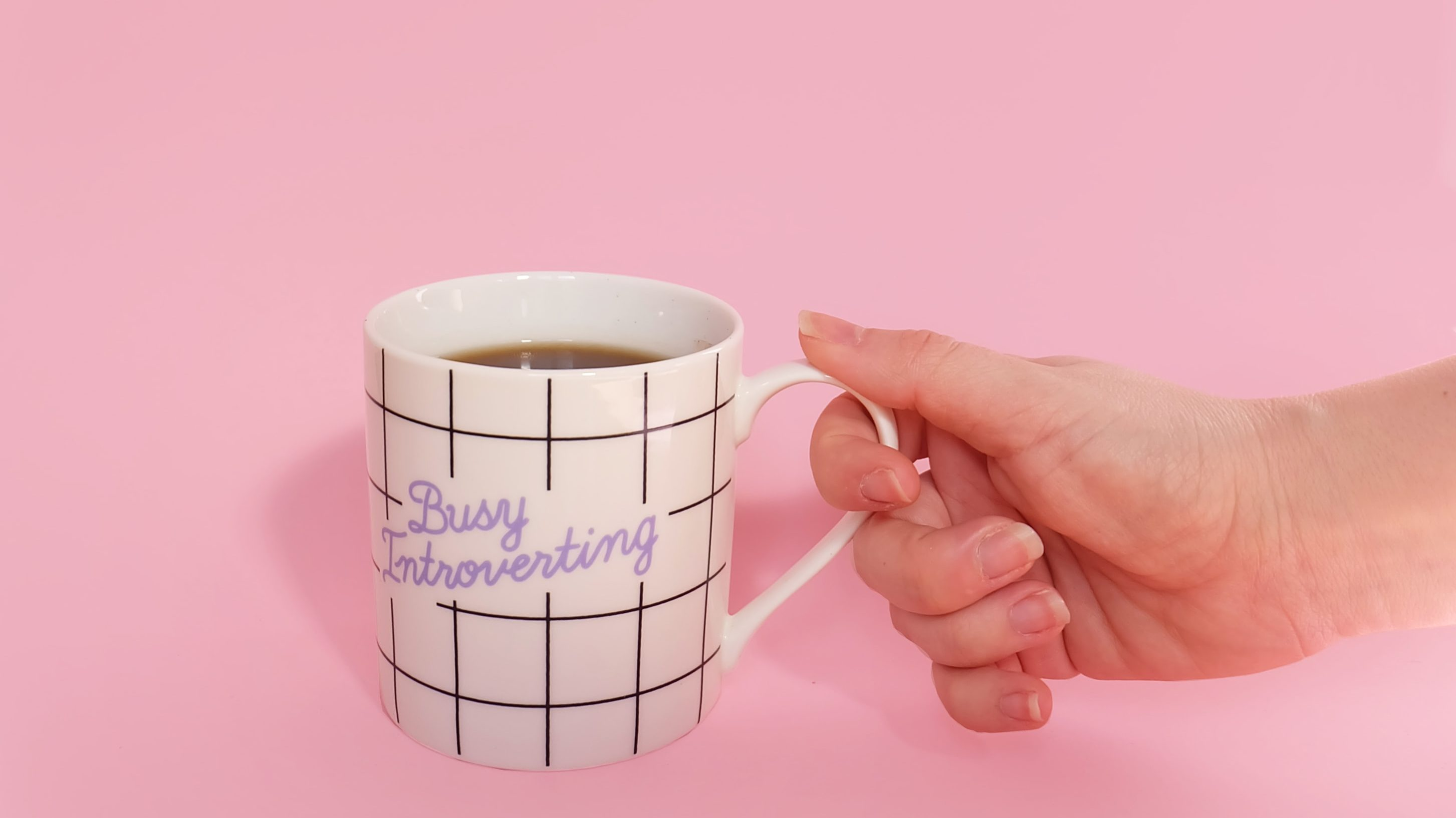 "A hand holding a mug that says ""busy introverting"" against a pink backdrop."
