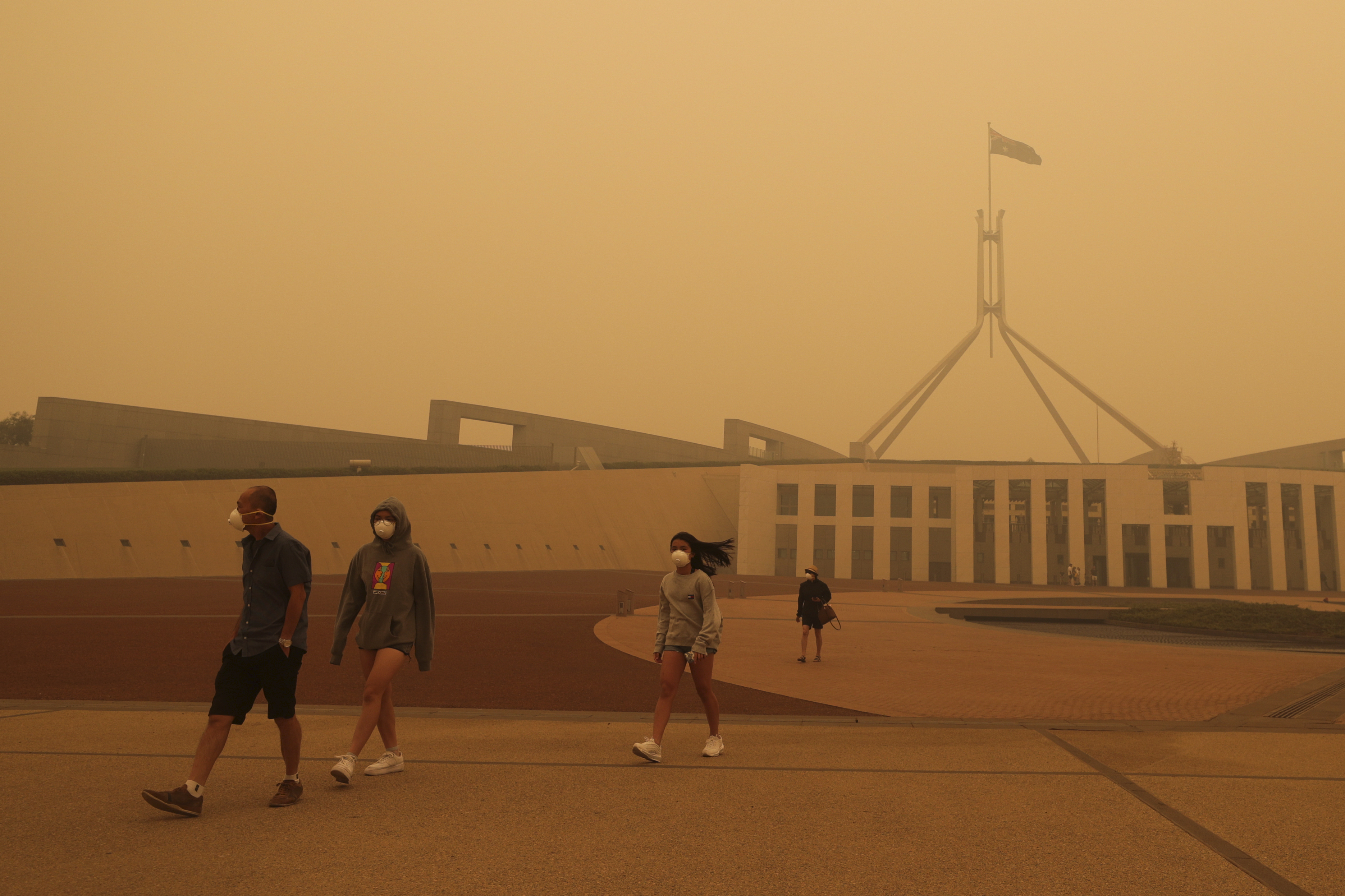 Four people walking outside an Australian museum in haze and smoke with masks on