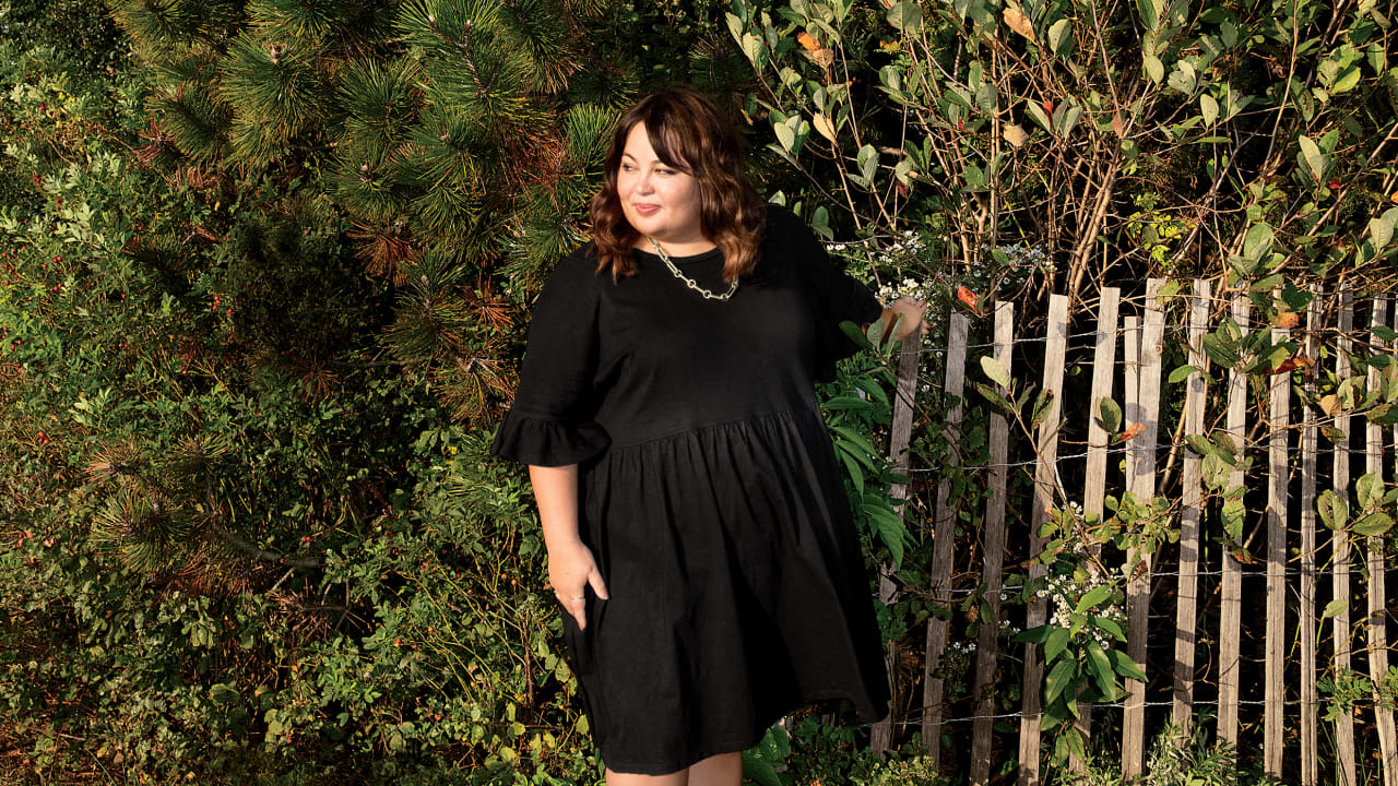 Aki Carpenter posing next to a fence abutting a forest.
