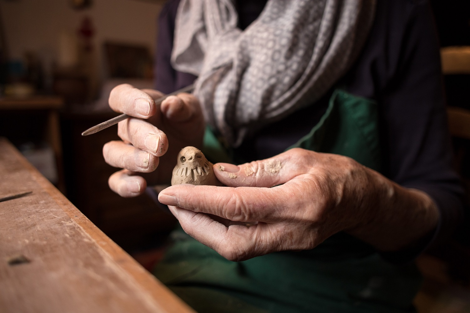 A woman molds a ball of clay into a bird shape using a putty knife.