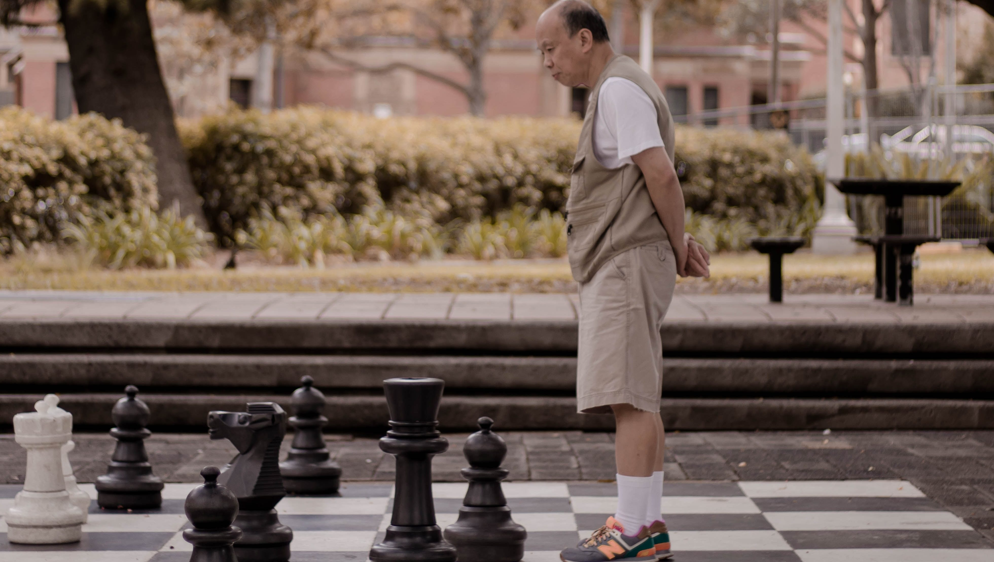 An older person standing on a life-size chessboard in a park.