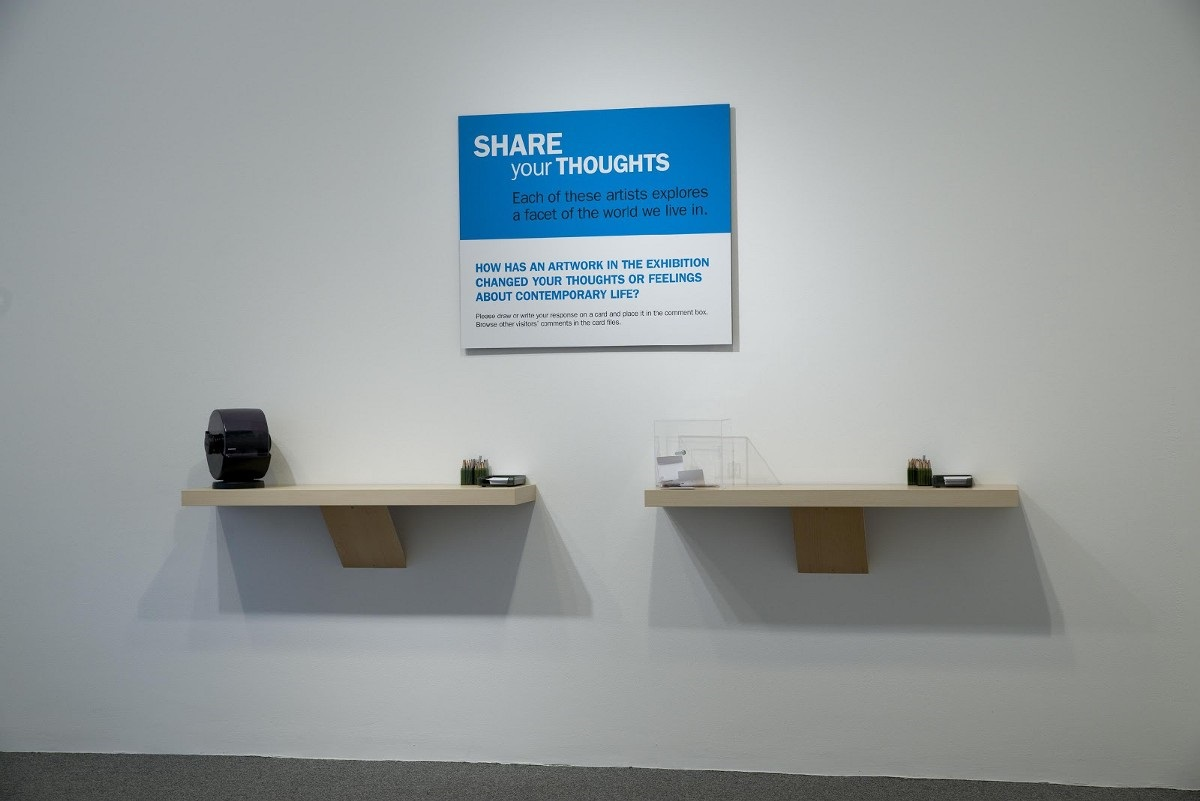 "Two floating shelves with note cards, pencils, and a rolodex on them, beneath as sign that says ""Share your thoughts: Each of these artists explores a facet of the world we live in. How has an artwork in the exhibition changed your thoughts or feelings about contemporary life?"""